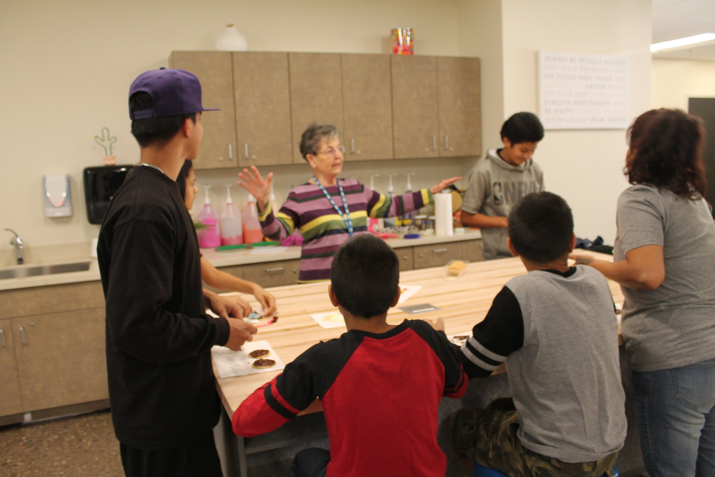 June Pomeroy helping the kiddos with frosting and sugar flowers decoration.