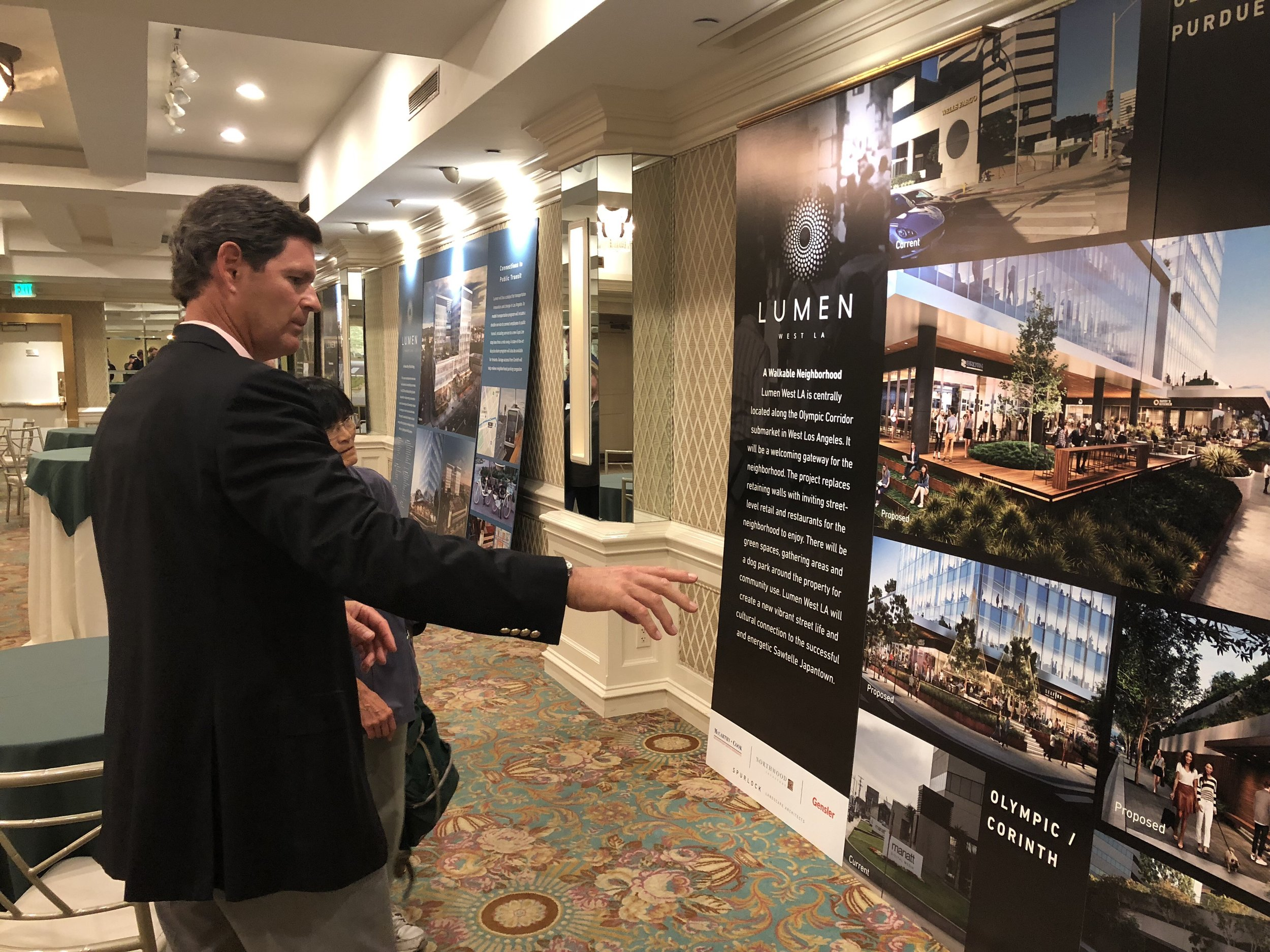 Developer Howard Cook points out details on the giant renders during the Trident / Lumen open house on Tuesday. The project will feature open floor plan offices, retail, and restaurants. The developers intend to find two large tenants to occupy the office spaces in the building.