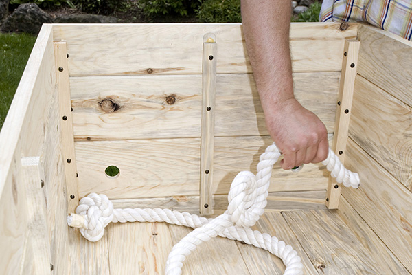Starting in a corner on the inside of the casket, feed the rope through one of the handle holes.
