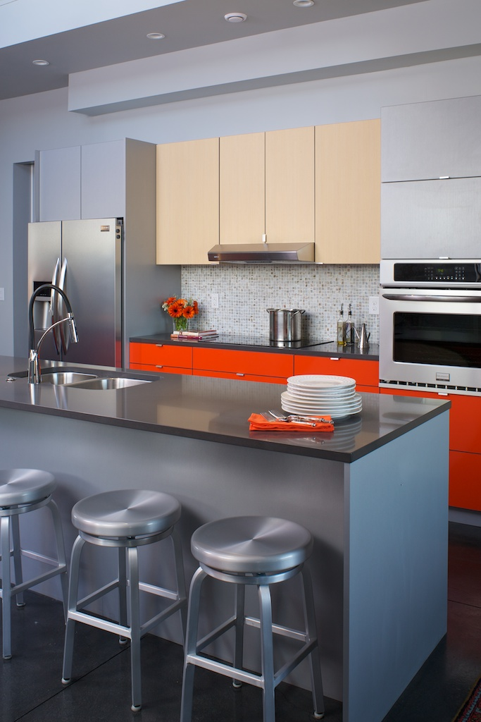 Why do one color when you can do three? Thanks to  kabi's extensive line of finishes mixing is always an option. Here the center islandis sheathed in the same material as the upper cabinets. The calmer colors allow the bright orange to popbut not overwhelm the space.
