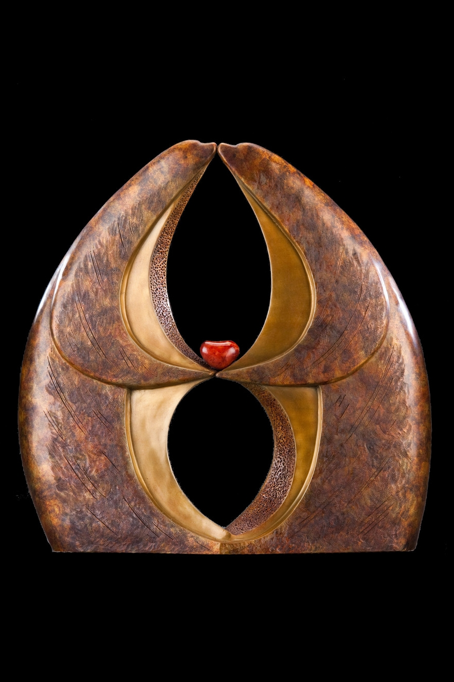 """Infinite Kiss Master  ,Bronze and Carnelian,18.5"""" H x 18"""" W x 6"""" D, Edition of 35:   These two creatures—bear, dolphin, seal-like yet uniquely their own—are forever  kissingand holding each other's heart. Their hands are separated indicating their  individualityand the partnership they have formed. At the same time, they are  connected at the base. A vertical infinity symbolweavesthroughout the piece  furtheremphasizing the eternal love flowing between the creatures."""
