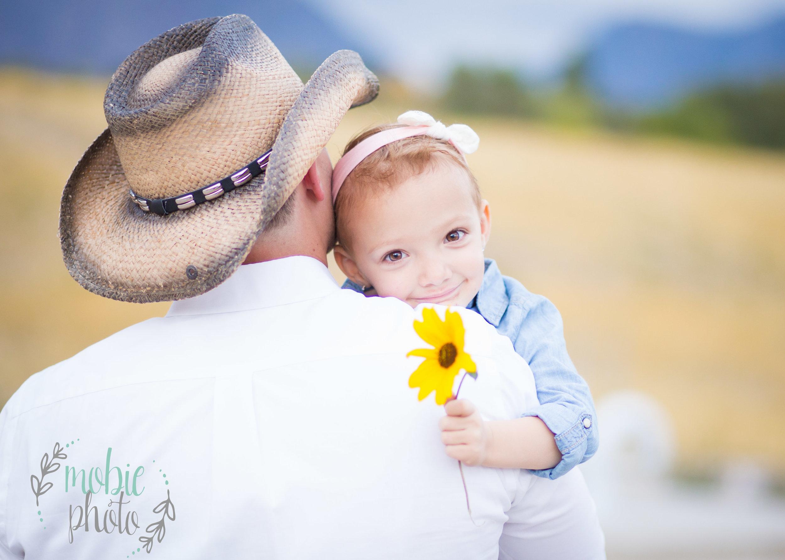Little girl hugging cowboy daddy