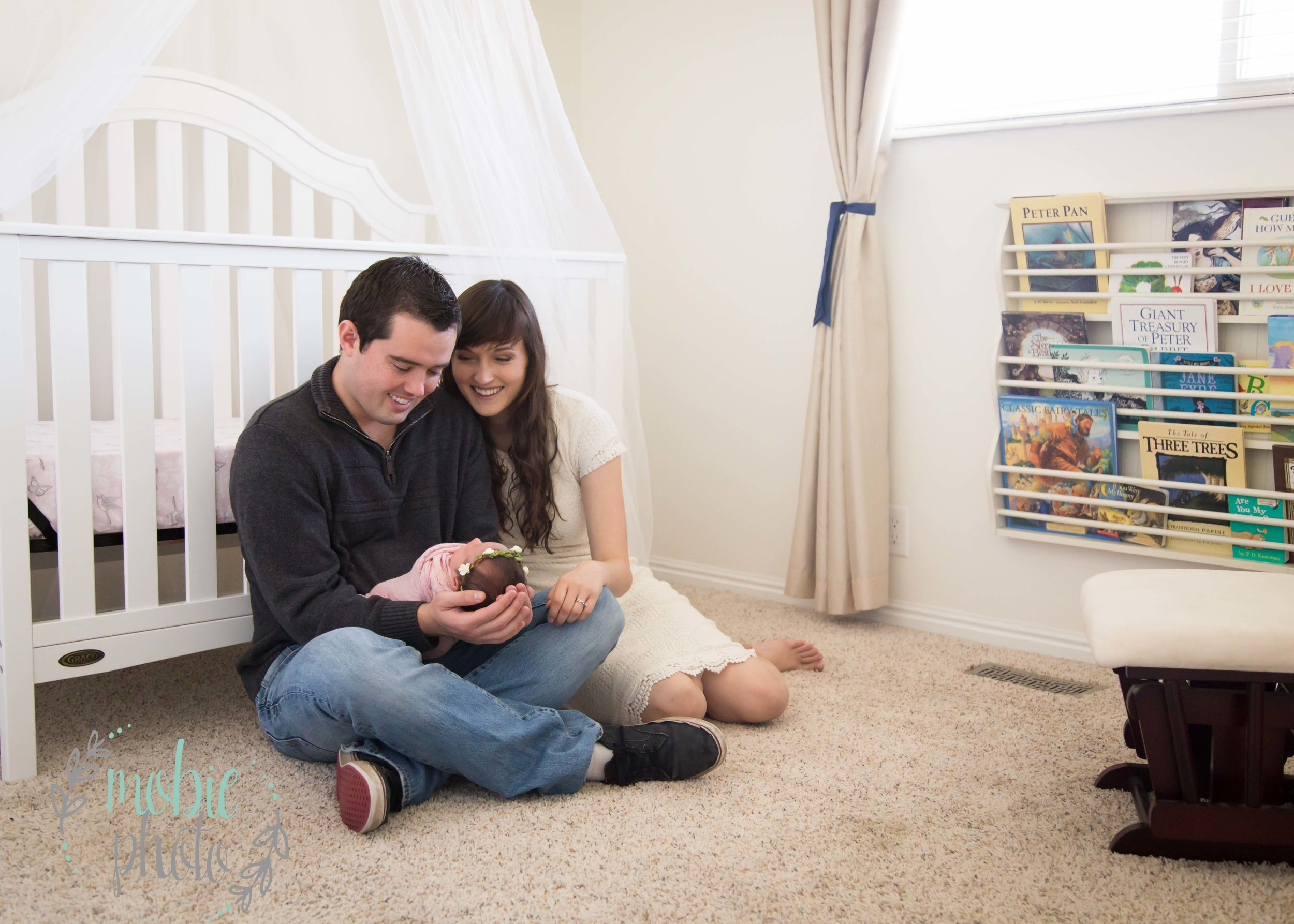 Newborn Photography Ideas - Parents holding Newborn Girl in Nursery