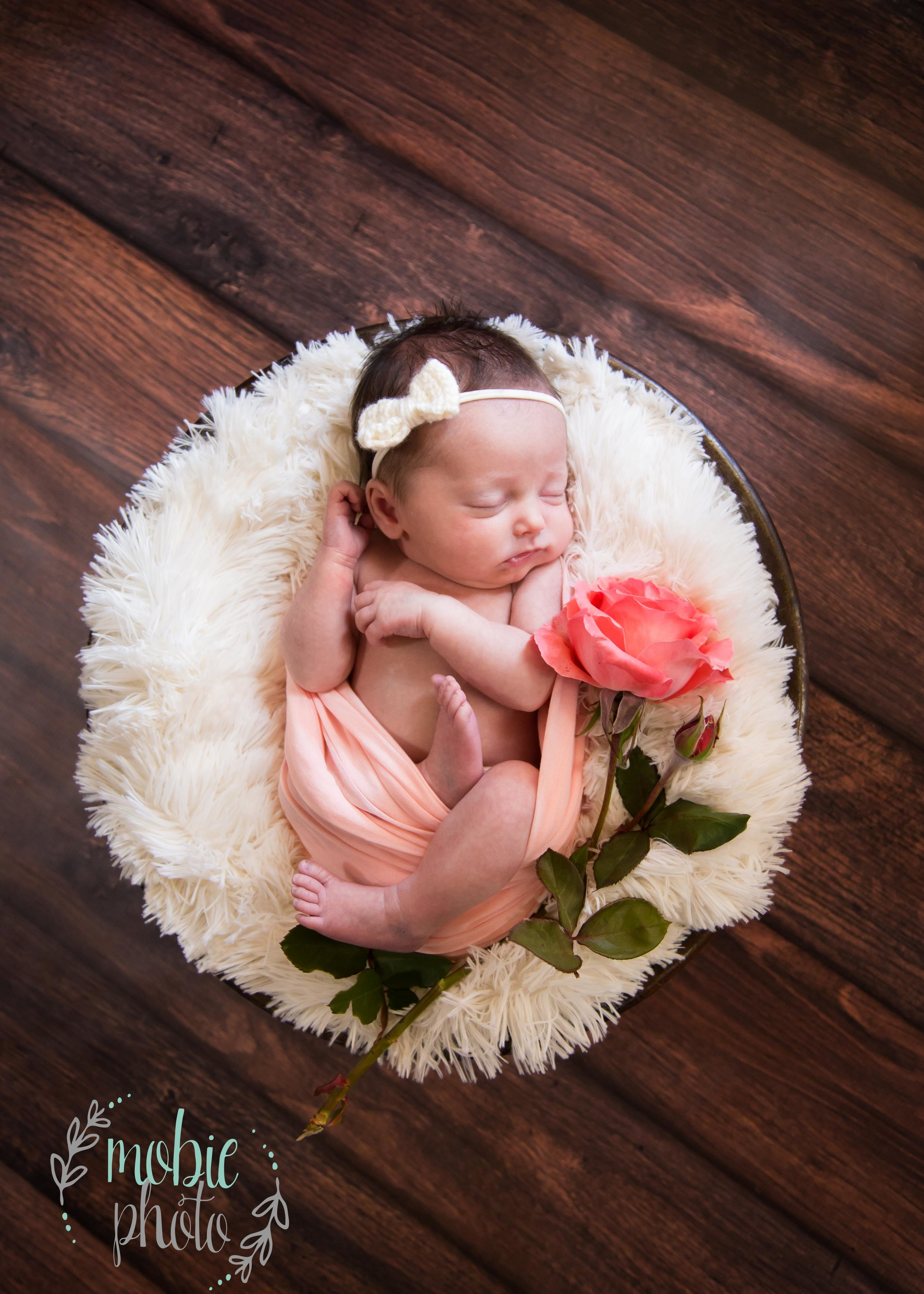 Newborn Girl in Round Basket with White Fluff, Pink Rose, and Pink Wrap