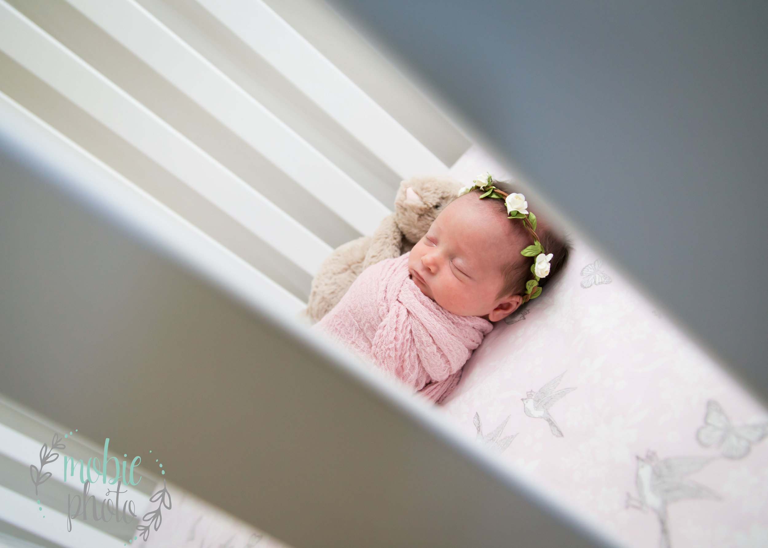 Newborn Girl Asleep in Crib with Stuffed Bunny, Pink Wrap, and Flower Headband