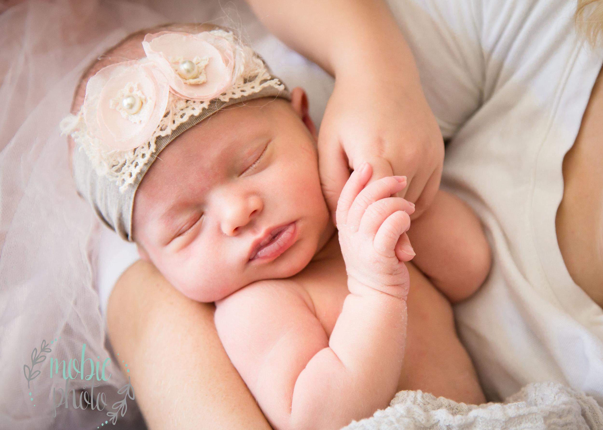 Newborn girl holding big sister's hand