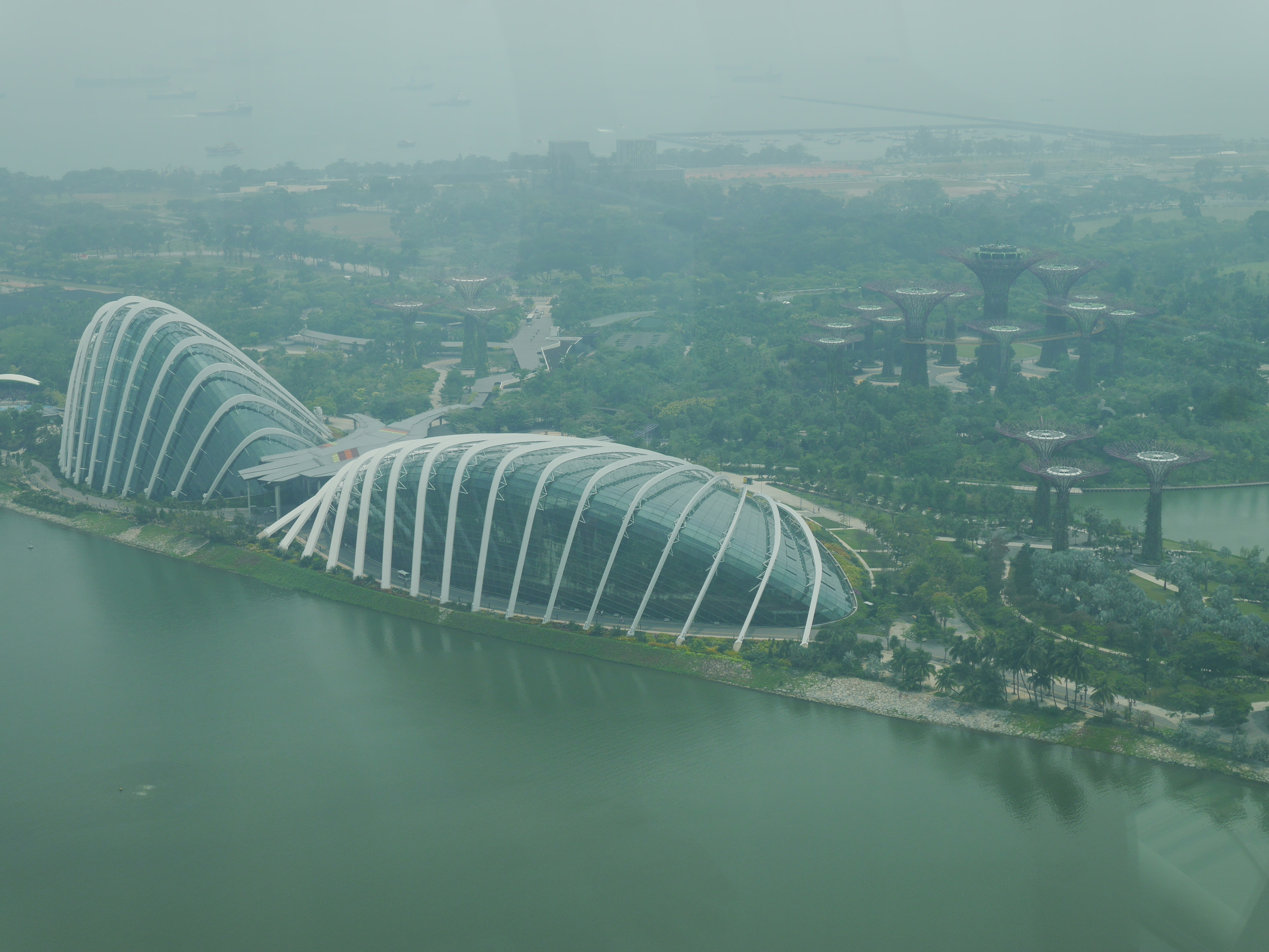 The Gardens by the Bay from above. Cloud Forest dome on the left, Flower Dome in the middle, and the Supertree Grove towards the back right.