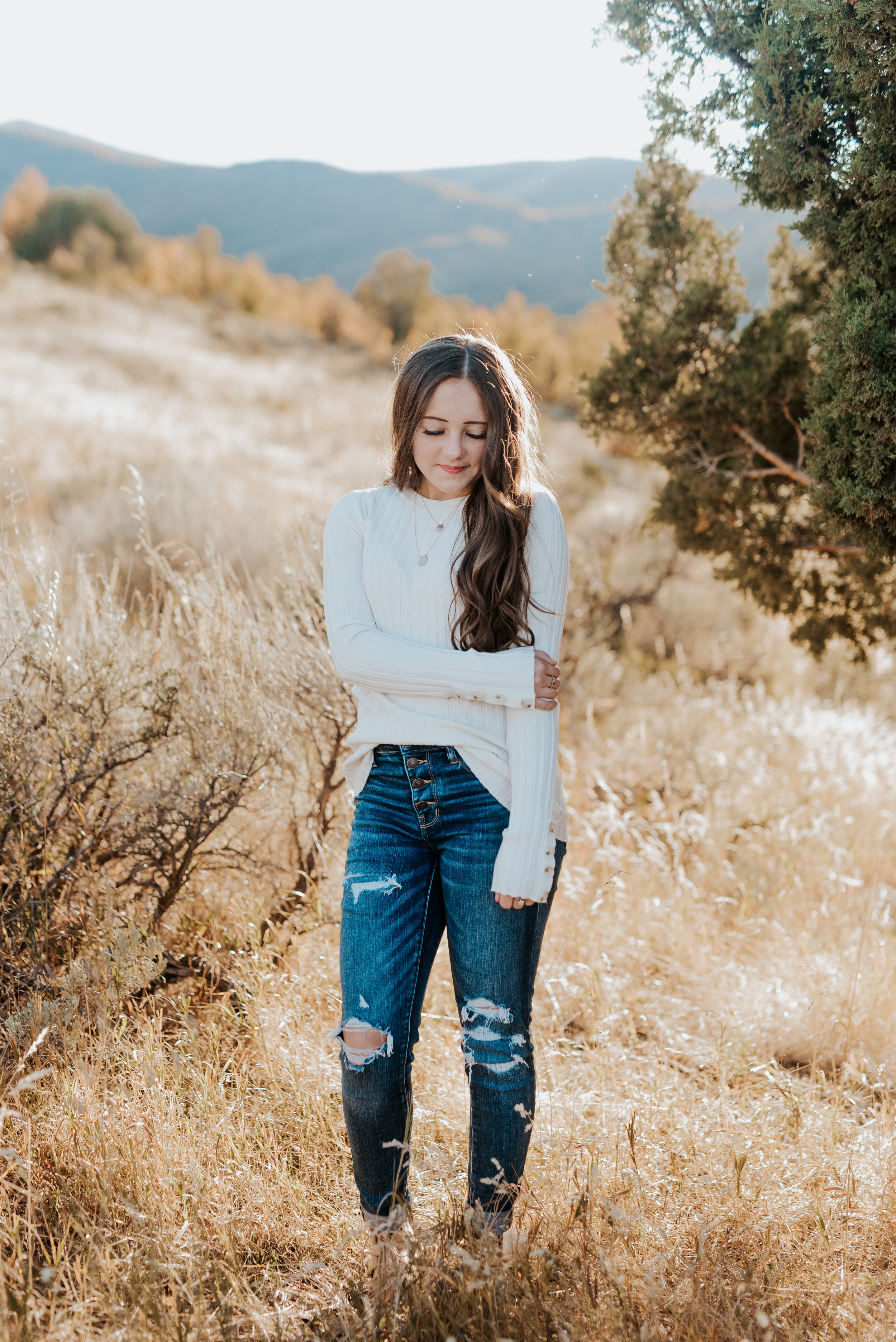 High school girl with long wavy brunette hair wearing a white sweater and dark wash denim in a golden field. teen fashion senior pictures photo session outfit inspiration casual senior picture outfits senior in high school graduating class of 2020 professional photographers in utah cache valley logan utah photographers #kristialysephotography #professionalphotographersinutah #utahphotographers #seniorportraits #cachevalley #loganutah #casualseniorpictureoutfits #teenfashion #senior #classof2020