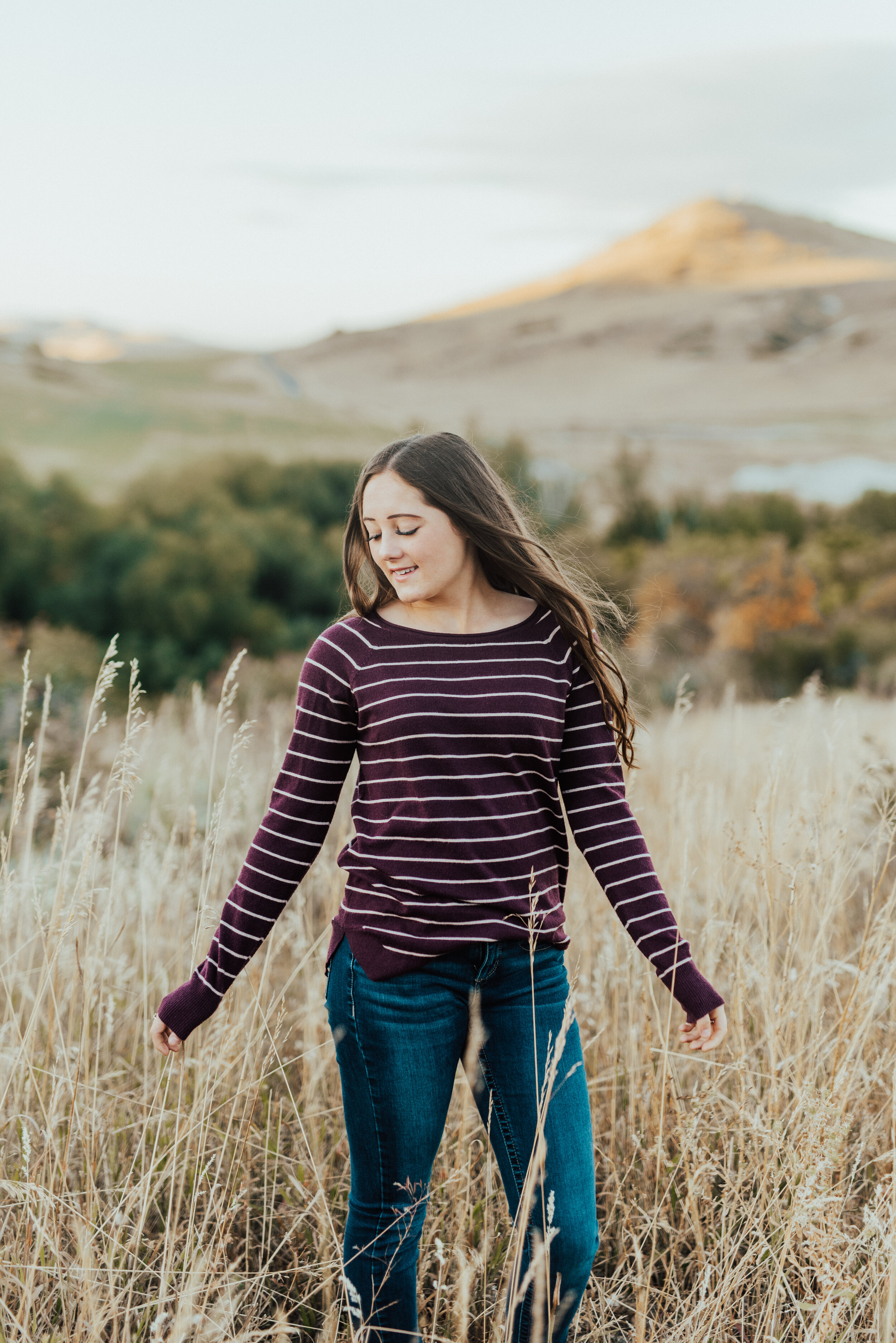 Teen girl in jeans and a burgundy striped sweater standing in a beautiful field. cache valley senior photo poses logan utah photographers teen fashion senior pictures photo session outfit inspiration casual senior picture outfits senior in high school graduating class of 2020 professional photographers in utah #kristialysephotography #professionalphotographersinutah #utahphotographers #seniorportraits #cachevalley #loganutah #casualseniorpictureoutfits #teenfashion #senior #classof2020