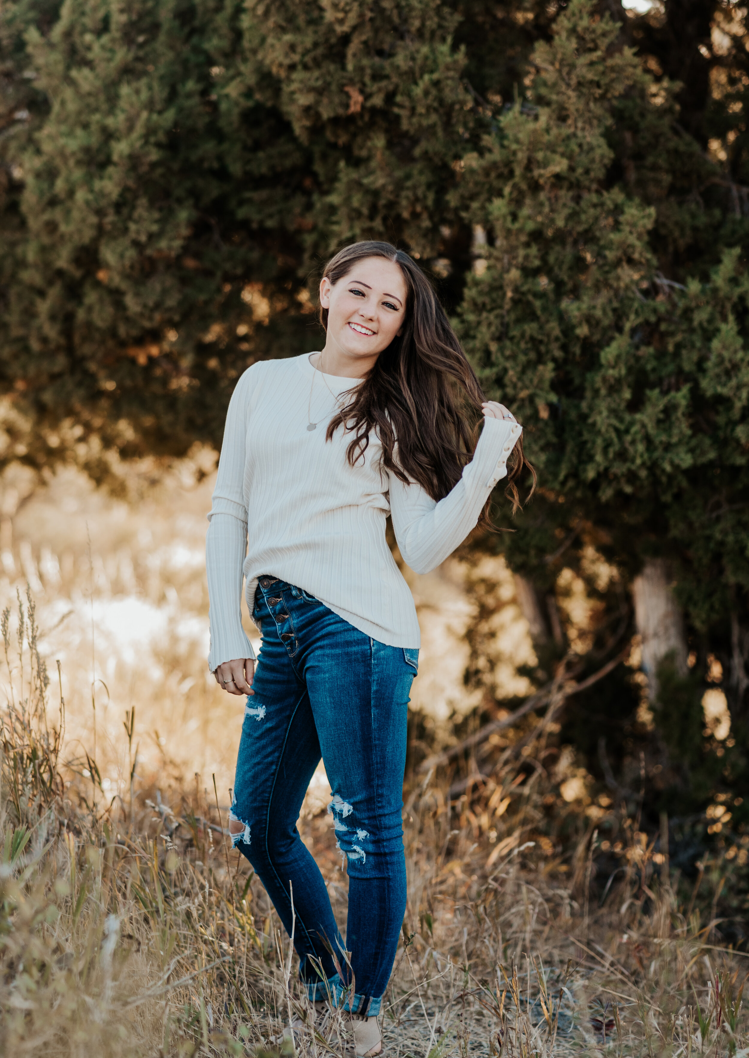 Girl rocking a white sweater and jeans in a field in the countryside of Cache Valley. professional photographers in utah cache valley senior photo poses logan utah photographers teen fashion senior pictures photo session outfit inspiration casual senior picture outfits senior in high school graduating class of 2020 #kristialysephotography #professionalphotographersinutah #utahphotographers #seniorportraits #cachevalley #loganutah #casualseniorpictureoutfits #teenfashion #senior #classof2020