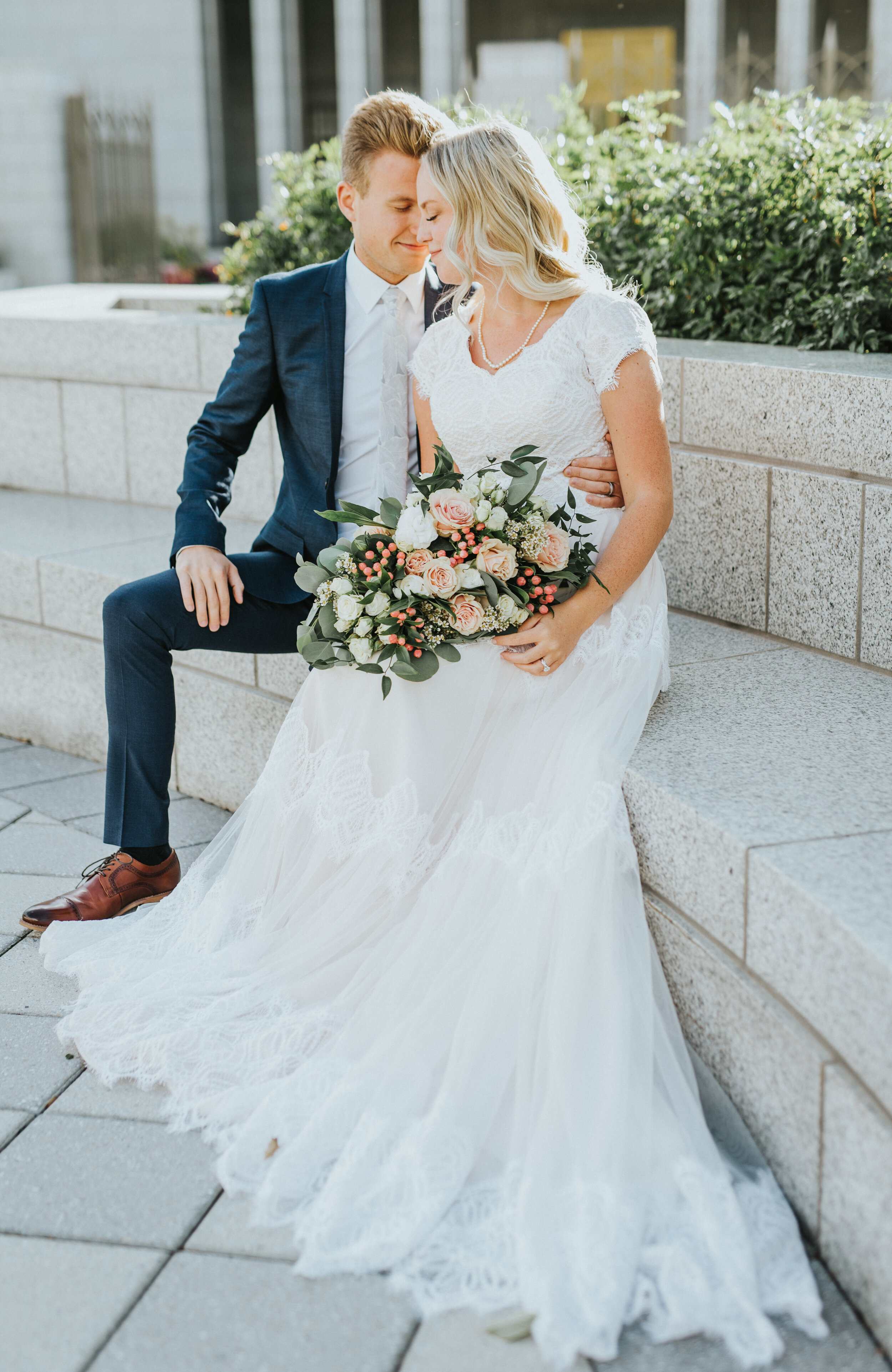 couple_sitting_on_bench_in_wedding_clothes.JPG