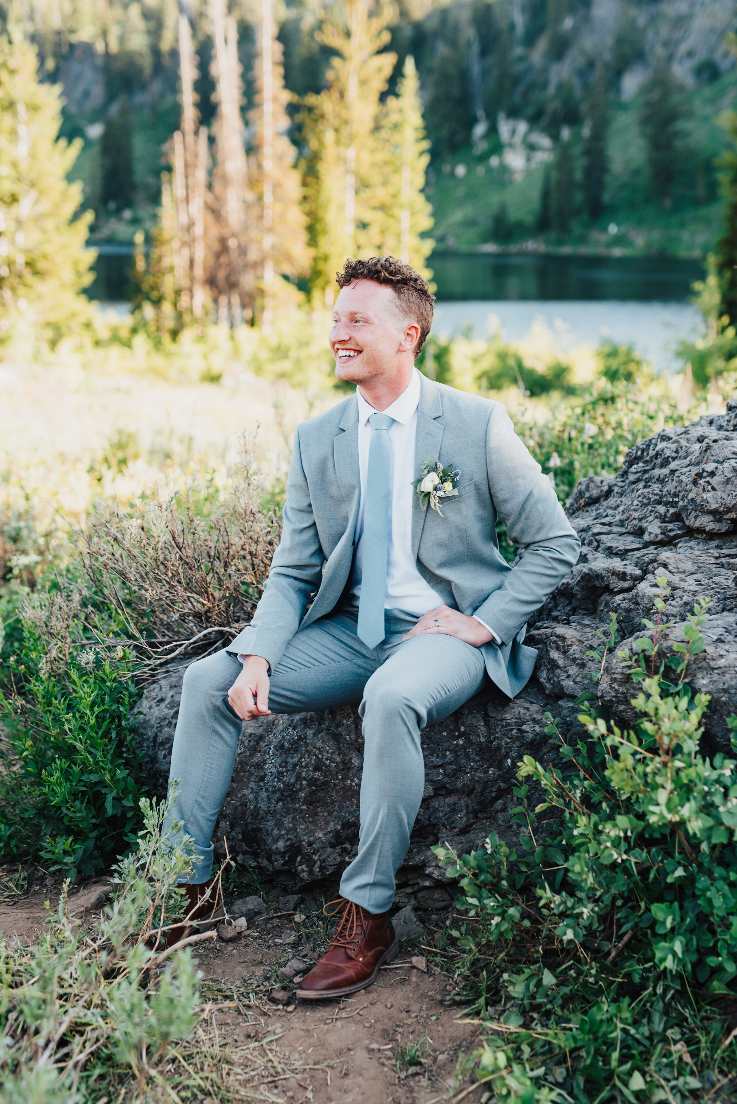 Dapper groom in grey suit wearing a handcrafted boutonnière during this lovely bridal session up Logan canyon. Kristi Alyse photography Logan Utah wedding photographer forest nature dreamy formals Logan canyon Tony Grove scenic bridals Northern Utah photographer Utah brides bride and groom Cache Valley #kristialysephotography #loganutahphotographer #tonygrove #logancanyon #utahweddingphotographer #bridals #formals #wildflowers #northernutah #utahbrides