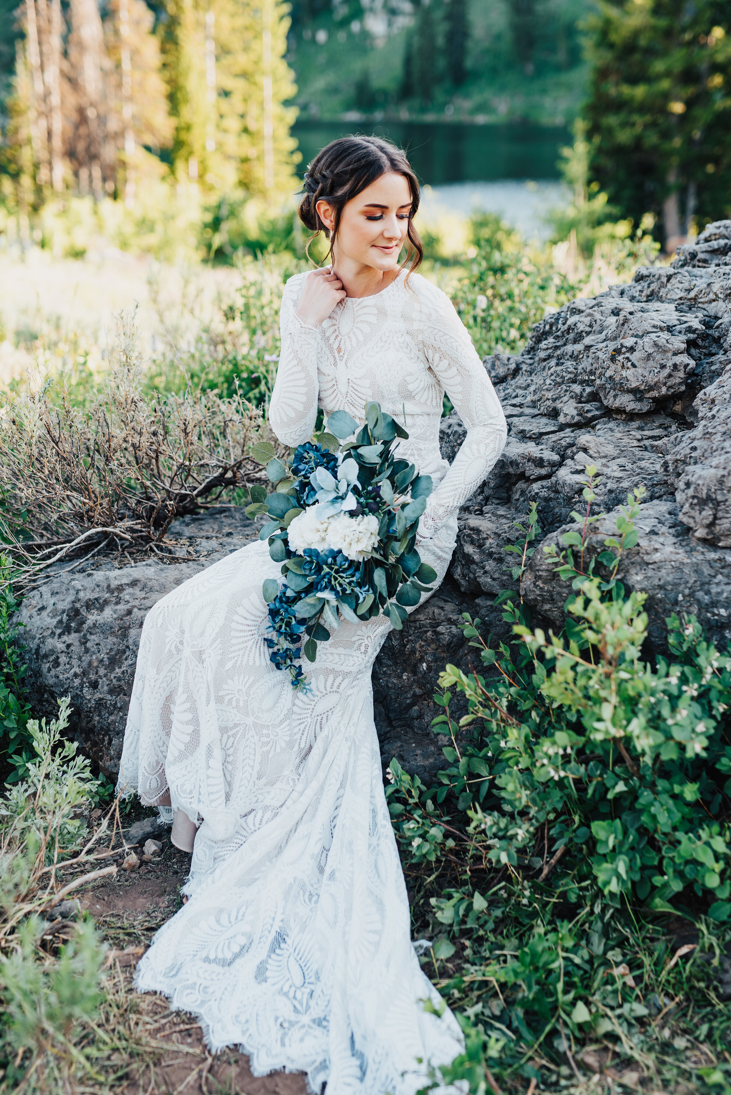 Glowing bride holding handpicked greenery during this lovely bridal session up Logan canyon. Kristi Alyse photography Logan Utah wedding photographer forest nature dreamy formals Logan canyon Tony Grove scenic bridals Northern Utah photographer Utah brides bride and groom Cache Valley #kristialysephotography #loganutahphotographer #tonygrove #logancanyon #utahweddingphotographer #bridals #formals #wildflowers #northernutah #utahbrides