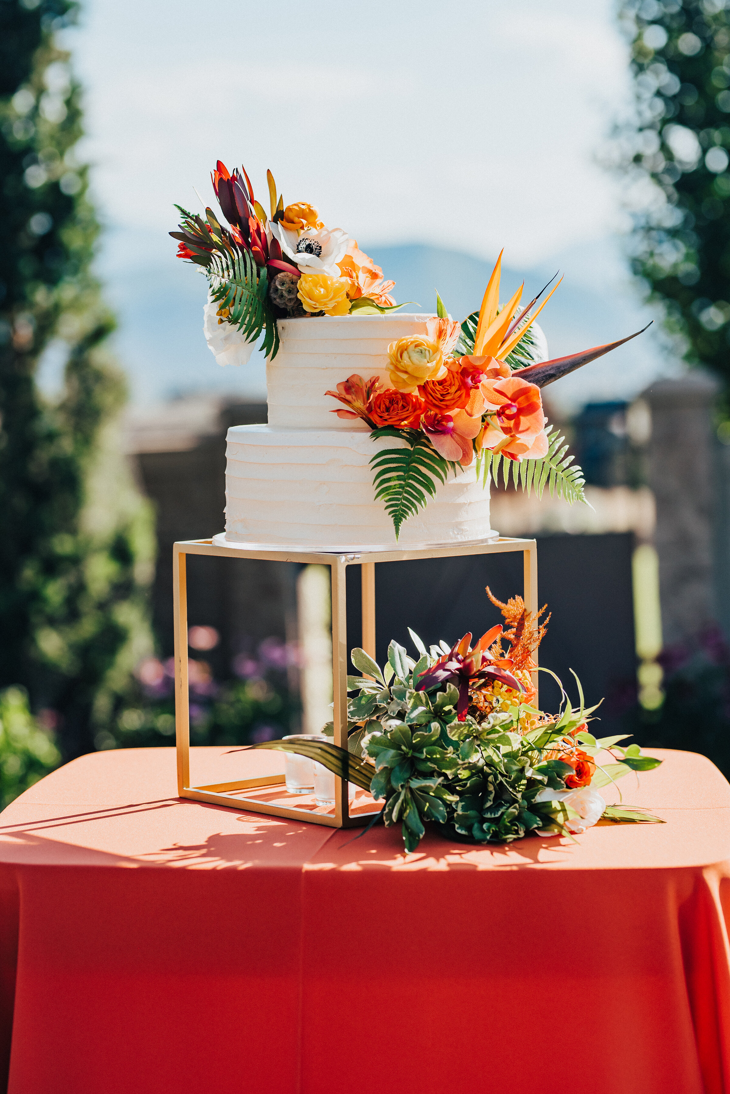 Gorgeous two-tier wedding cake with floral accents displayed at this lovely backyard wedding in Park City. Kristi Alyse Photography Logan Utah photographer Park City wedding photographer Drive-Thru wedding COVID wedding neon signs socially distant wedding bride and groom wedding cake #kristialysephotography #weddingphotographer #utahweddings #parkcity #utahbrides #drivethruwedding #covidwedding #LoganUtahphotographer #utahweddingphotographer #weddingcake