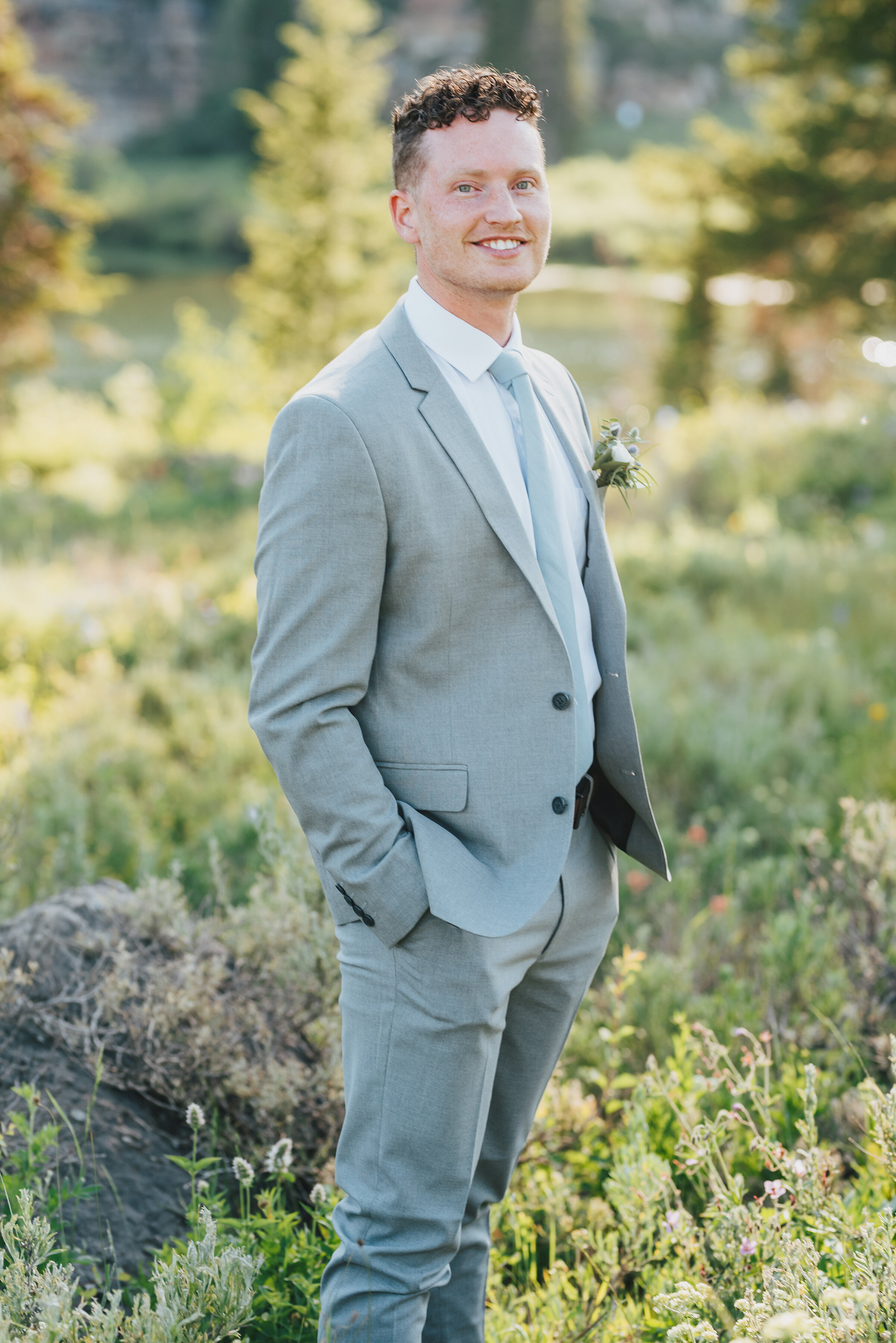 Handsome groom in grey suit surrounded by wild flowers for his formals up Logan canyon. Kristi Alyse photography Logan Utah wedding photographer forest nature dreamy formals Logan canyon Tony Grove scenic bridals Northern Utah photographer Utah brides bride and groom Cache Valley #kristialysephotography #loganutahphotographer #tonygrove #logancanyon #utahweddingphotographer #bridals #formals #wildflowers #northernutah #utahbrides