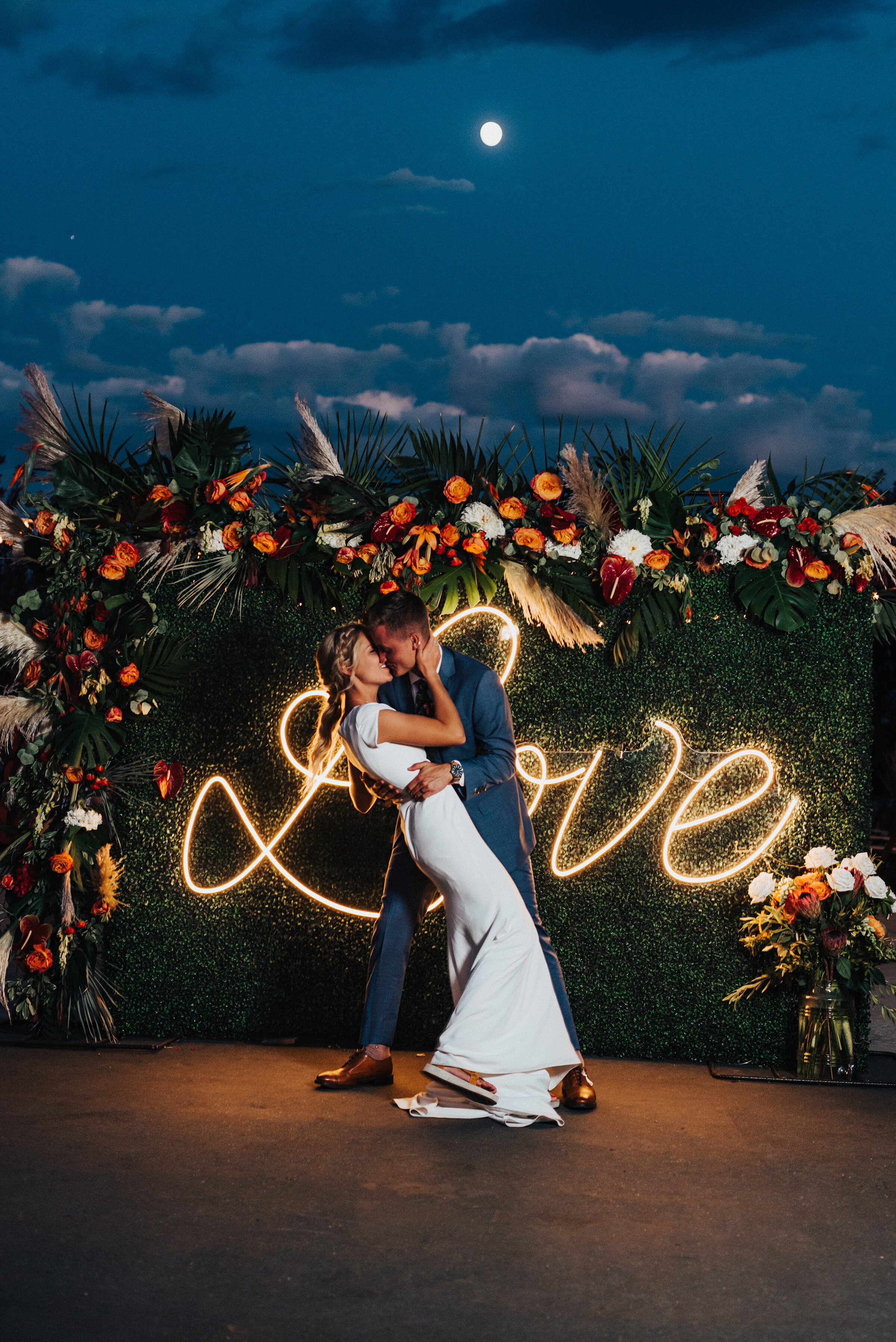 Gorgeous couple in front of neon sign and floral backdrop at this fun-loving backyard wedding reception in Park City. Kristi Alyse Photography Logan Utah photographer Park City wedding photographer Drive-Thru wedding COVID wedding neon signs socially distant wedding bride and groom #kristialysephotography #weddingphotographer #utahweddings #parkcity #utahbrides #drivethruwedding #covidwedding #LoganUtahphotographer #utahweddingphotographer