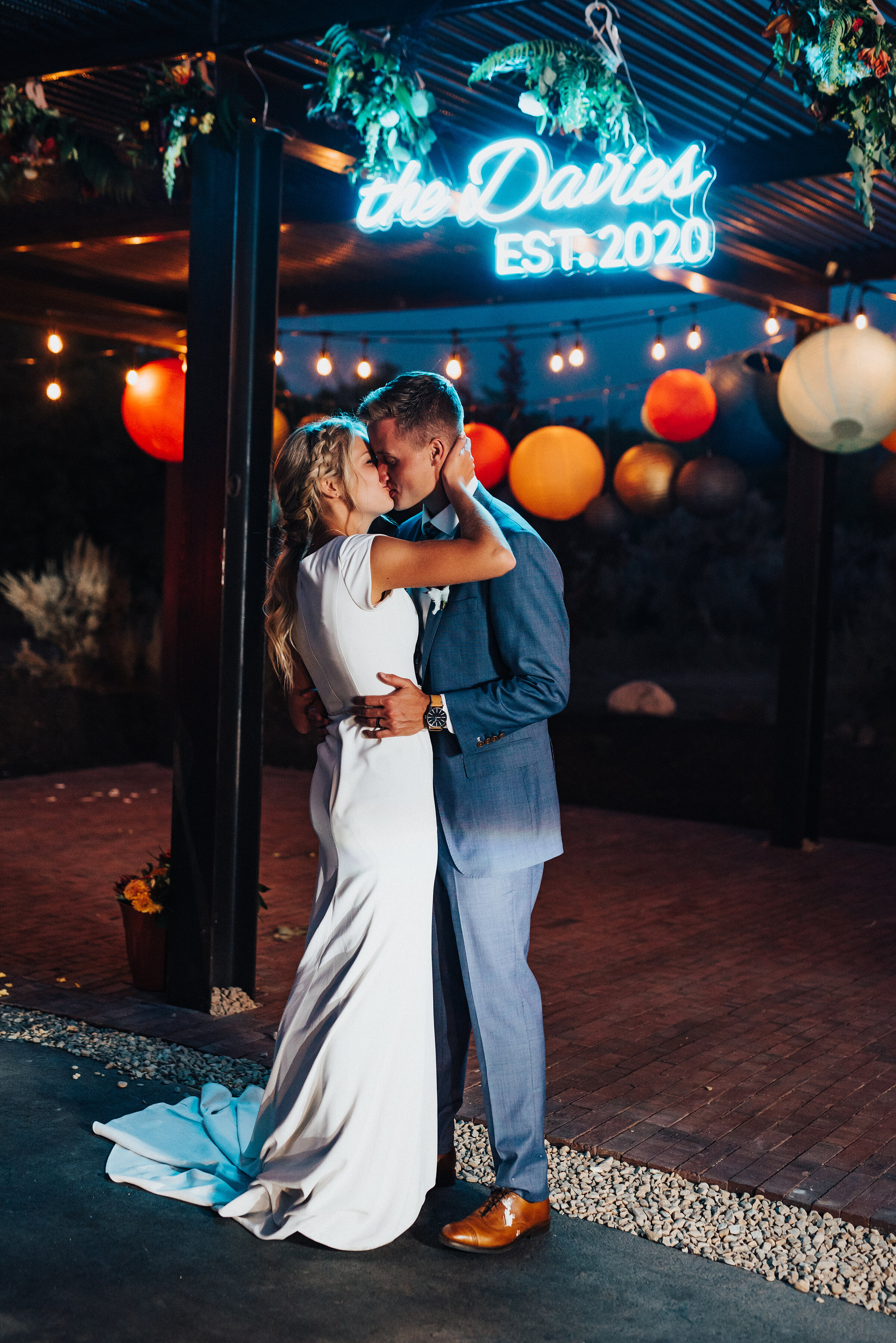 Retro neon sign hovering over this happy newlywed couple at their backyard wedding reception in Park City. Kristi Alyse Photography Logan Utah photographer Park City wedding photographer Drive-Thru wedding COVID wedding neon signs socially distant wedding bride and groom #kristialysephotography #weddingphotographer #utahweddings #parkcity #utahbrides #drivethruwedding #covidwedding #LoganUtahphotographer #utahweddingphotographer