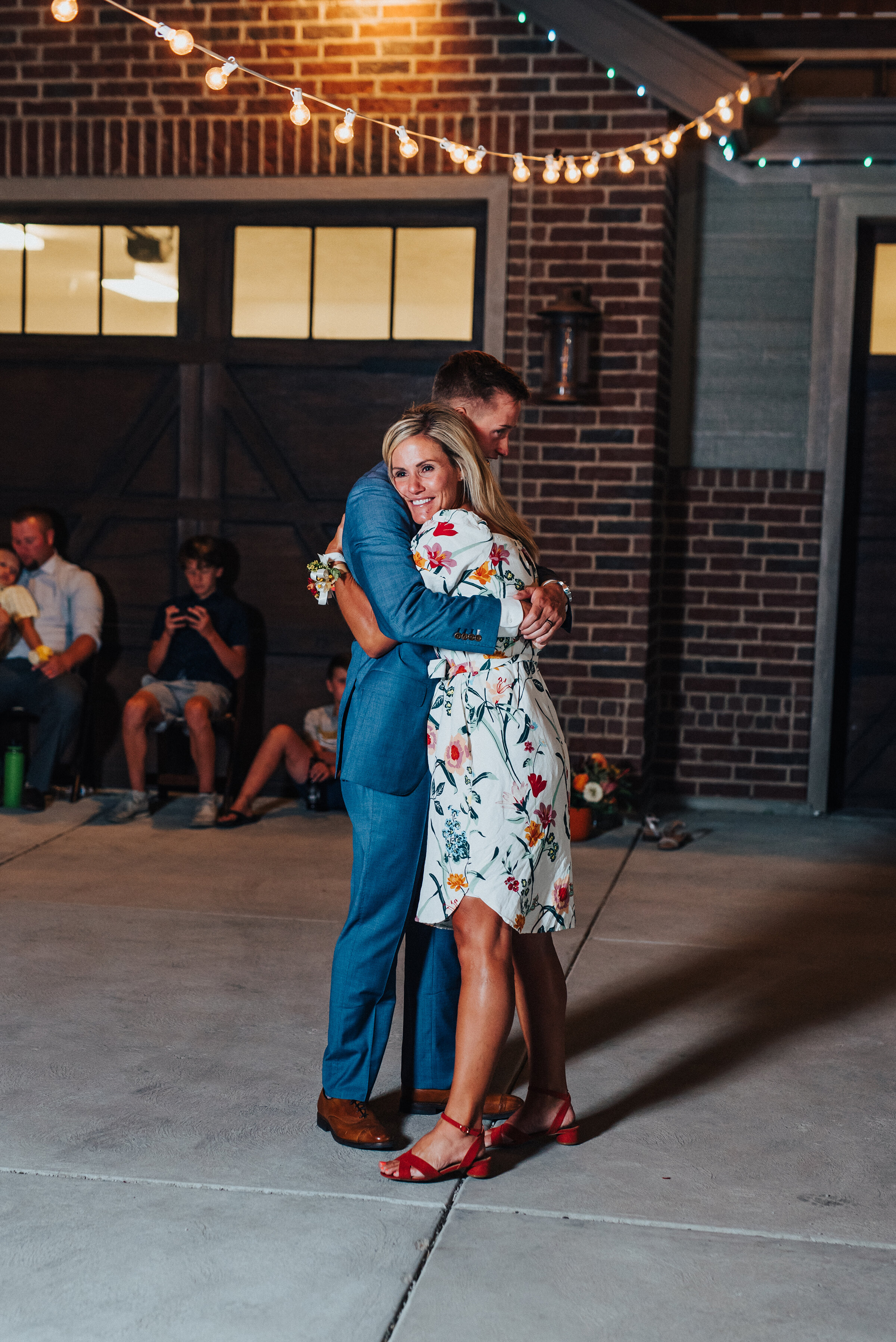Mother of the groom dancing with her son at this dreamy backyard wedding in Park City. Kristi Alyse Photography Logan Utah photographer Park City wedding photographer Drive-Thru wedding COVID wedding neon signs socially distant wedding bride and groom mother of the groom #kristialysephotography #weddingphotographer #utahweddings #parkcity #utahbrides #drivethruwedding #covidwedding #LoganUtahphotographer #utahweddingphotographer #motherofthegroom