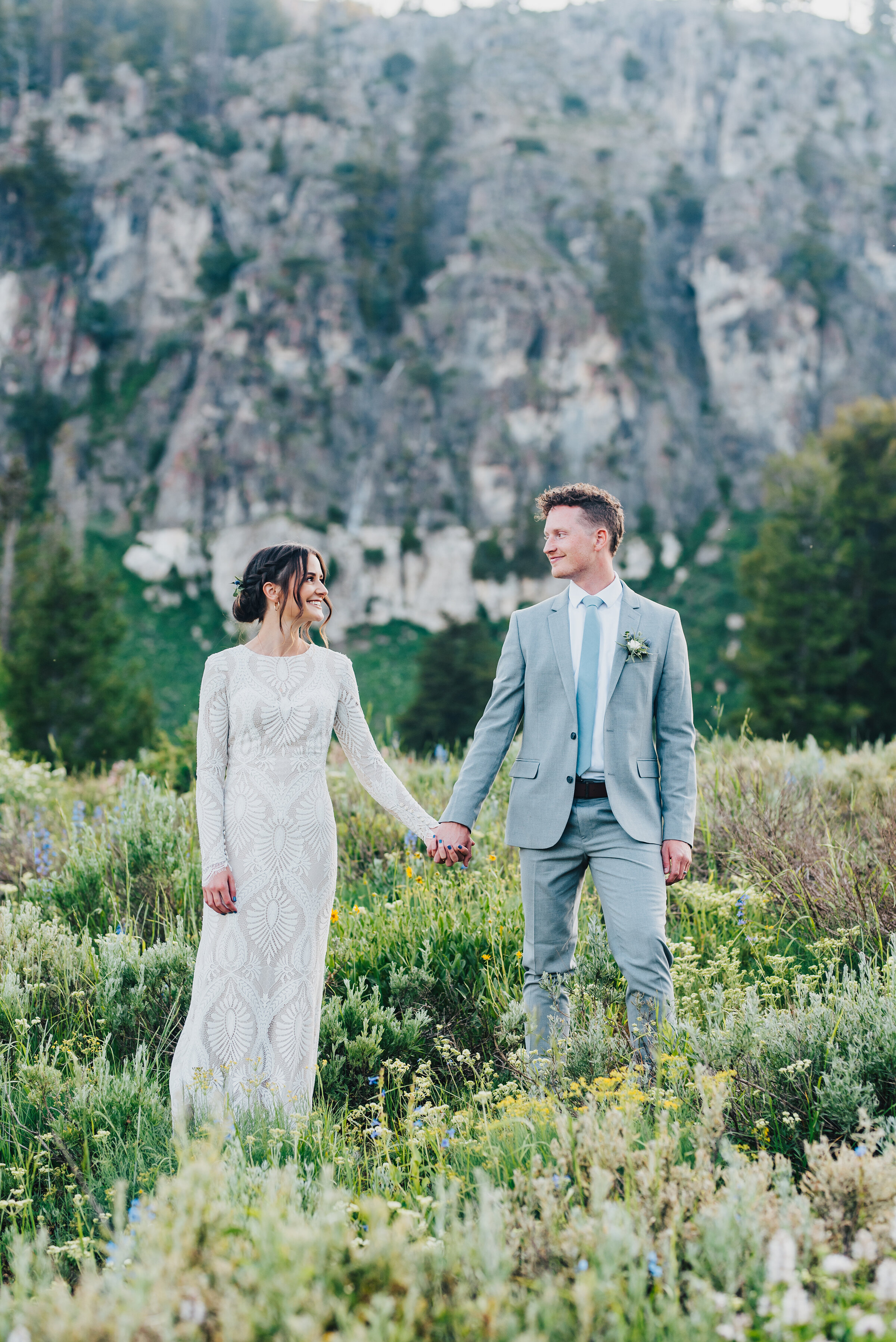 Two lovers holding hands in a meadow during their formals up Logan canyon at Tony Grove. Kristi Alyse photography Logan Utah wedding photographer forest nature dreamy formals Logan canyon Tony Grove scenic bridals Northern Utah photographer Utah brides bride and groom Cache Valley #kristialysephotography #loganutahphotographer #tonygrove #logancanyon #utahweddingphotographer #bridals #formals #wildflowers #northernutah #utahbrides