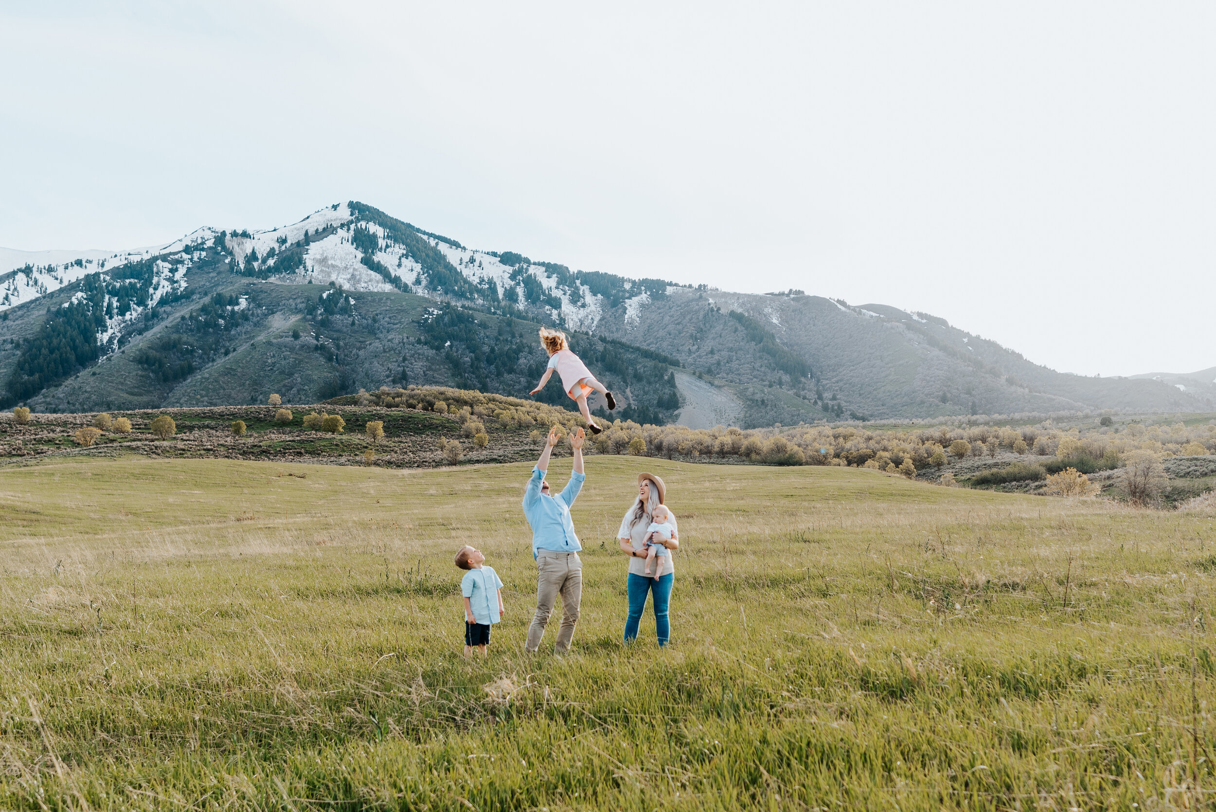 The Homer family poses as a group in the Wellsville Utah mountains for an unforgettable photoshoot. Dad throwing daughter for memorable family photoshoot funny family photo ideas Utah photography Logan Utah photographer Utah family photography Kristi Alyse Photography #kristialyse #kristialysephotography #loganphotography #familyphotoinspo #funnyfamilypics #fundad #wellsvillemountains #saycheese