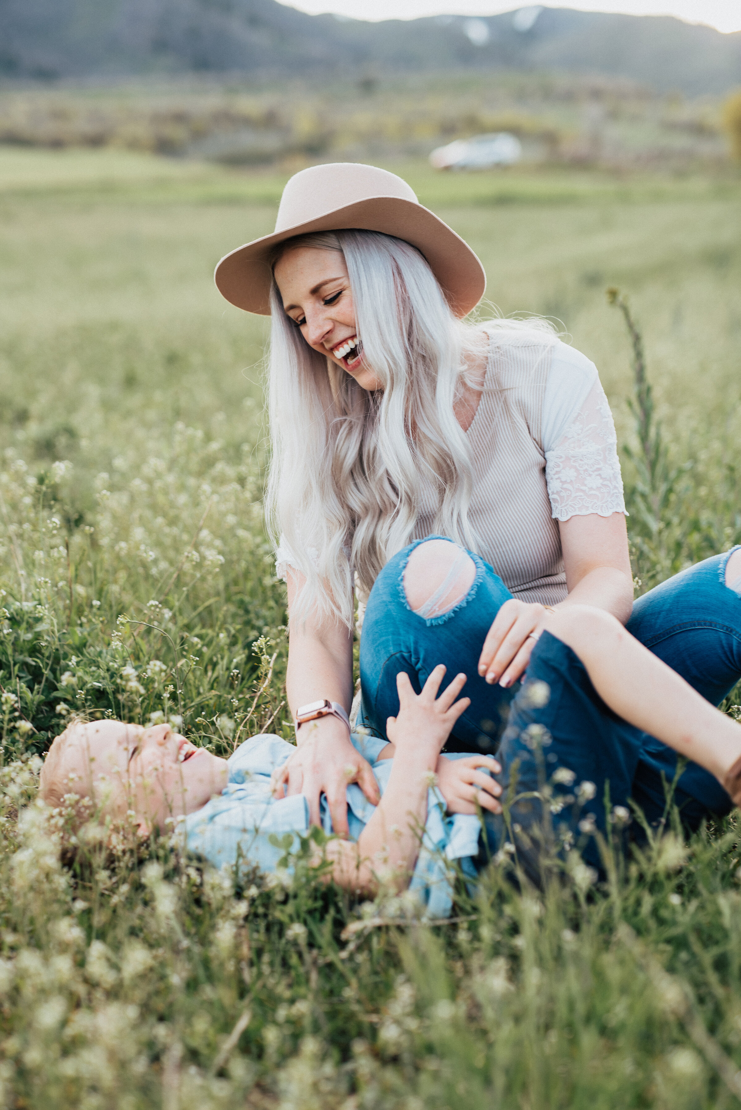 Mom laughs with son in the grass during a beautiful logan utah photography session with Kristi Alyse Photography. Mom of boys photo inspiration laughing photo ideas candid photography family portraits logan utah photographer laughter in photography #livelaugh #kristialysephotography #kristialyse #photography #photos #laughingportraits #momofboys #thatsmyboy #adventurephotoshoot