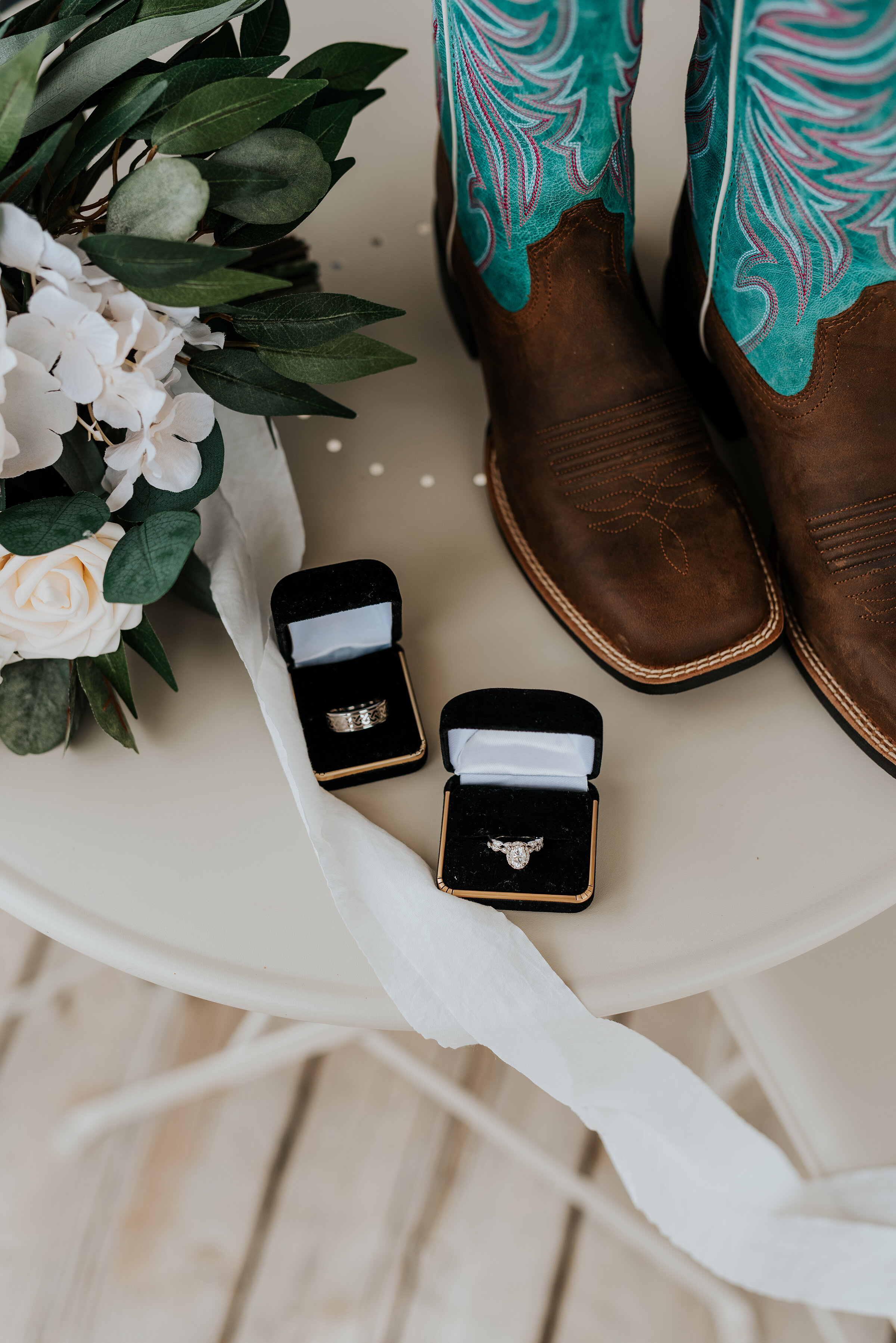 Accessories from this western rustic wedding day included cowgirl boots, a beautiful set of white roses and the bride and grooms wedding rings. Ephraim Utah photography wedding rings outdoor location western inspired rustic Airbnb photo aesthetic #ephraimutah #utahphotography #weddingdayphotography #gettingmarried #rusticwedding #utahwedding #westernstyle #weddingphotoshoot #weddingrings