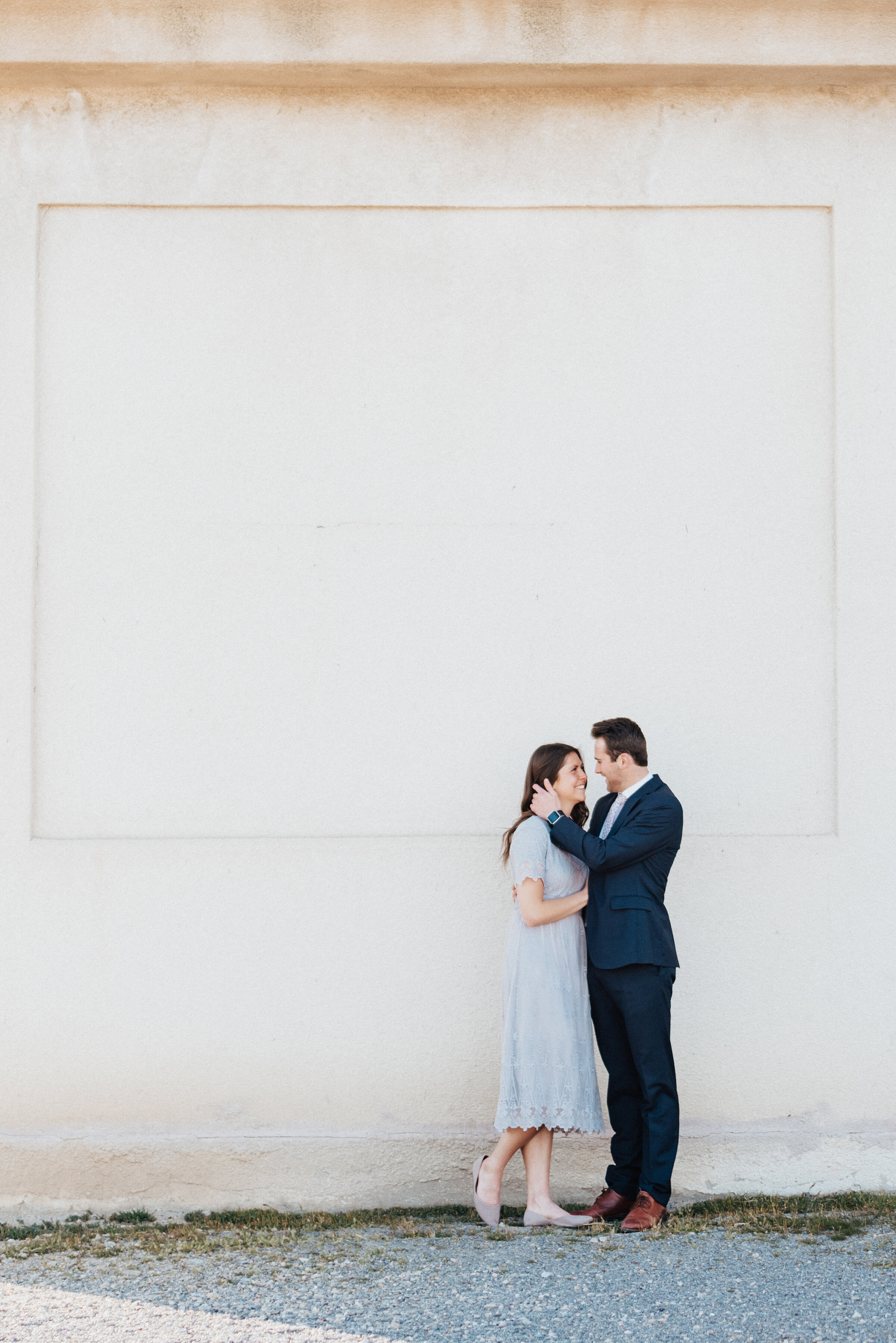 Beautiful matching couple pose in front of a large textured wall during their utah engagement photoshoot session with Kristi Alyse Photography. Utah's best photographer family photography gray lace dress outfit ideas for engagements utah engagement photoshoot Kristi Alyse photography session #kristialysephotos #engagementideas #utahengagements #outfitideas #matchingcouples #dresstoimpress #photographyinspo #texturedphotos