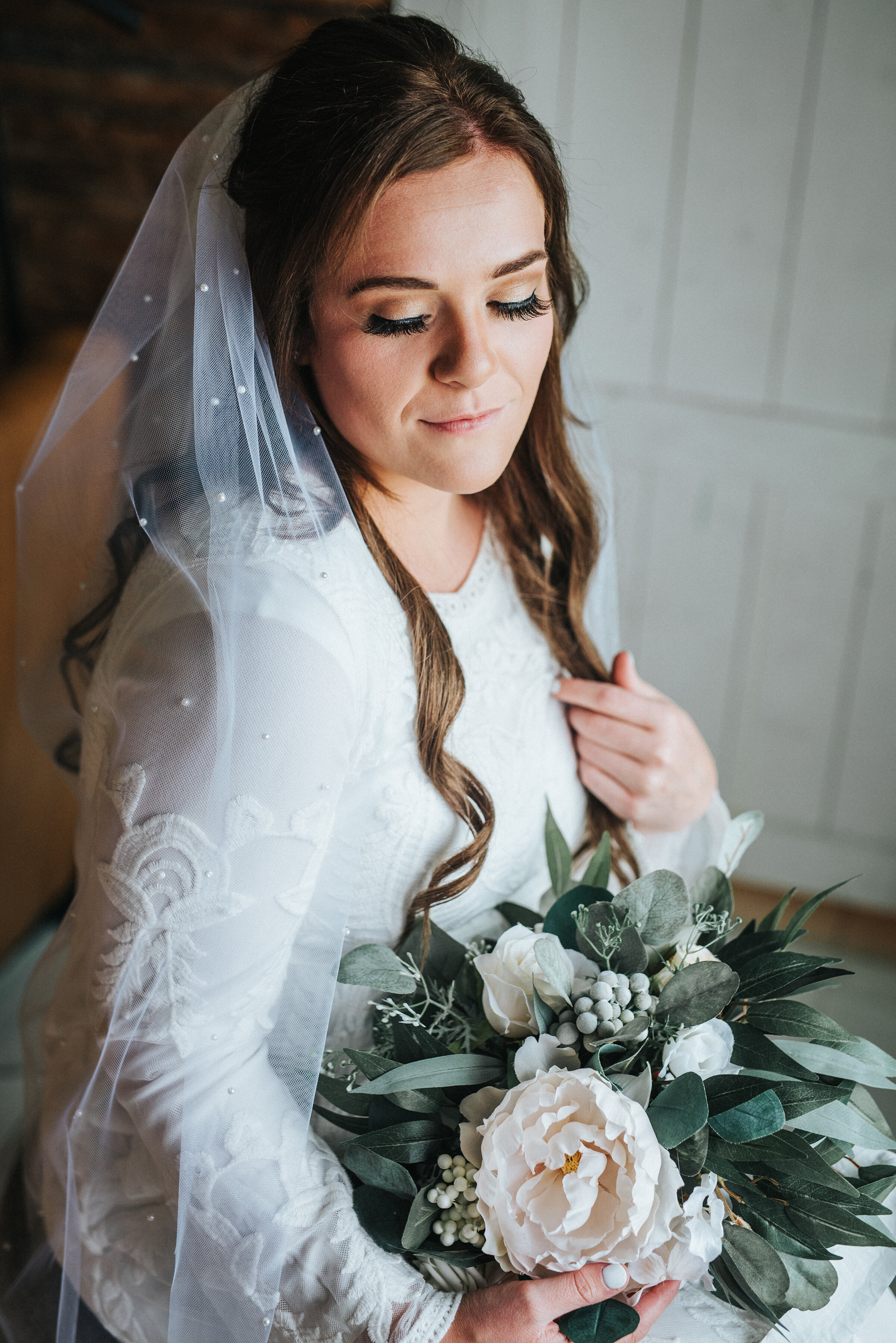 The bride absolutely glowing after the final touches were applied on her wedding day. The curls in her hair and the makeup applied were stunning and her veil was just the right accent piece. Wedding day photoshoot in Ephraim Utah photography wedding outdoor location western inspired rustic Airbnb photo aesthetic #ephraimutah #utahphotography #weddingdayphotography #gettingmarried #rusticwedding #utahwedding #westernstyle #weddingphotoshoot