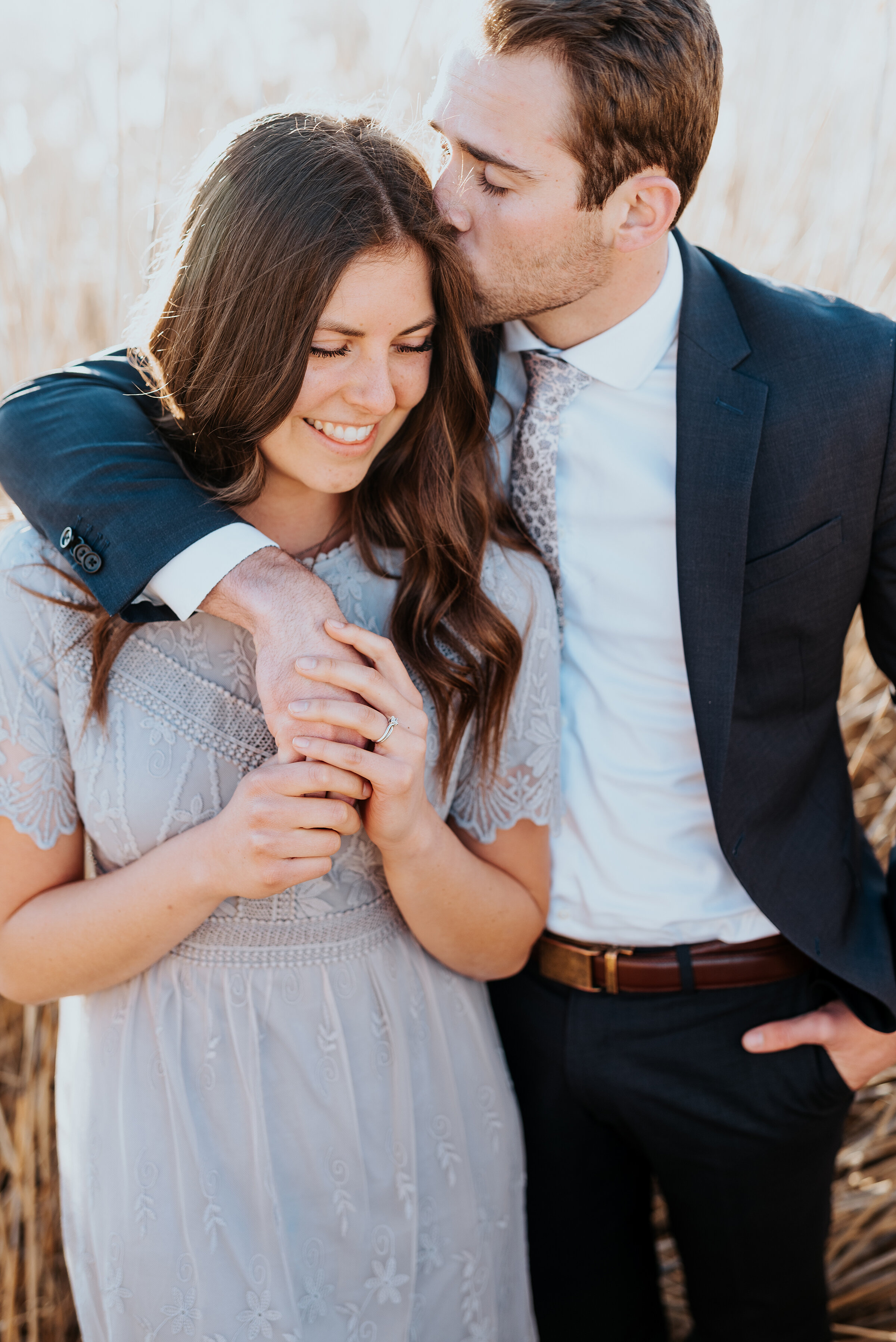 Man kisses his fiancé' head while she looks stunning in a gray lace dress during their engagement photoshoot. Kissing couple during their engagement photoshoot magna utah gray aesthetic outdoor photoshoot Kristi Alyse photography best utah photographer engagement session ideas #engagementideas #outdoorphotoshoot #grayaesthetic #kissinginatree #capturingmemories #kristialysephotography #utahengagements
