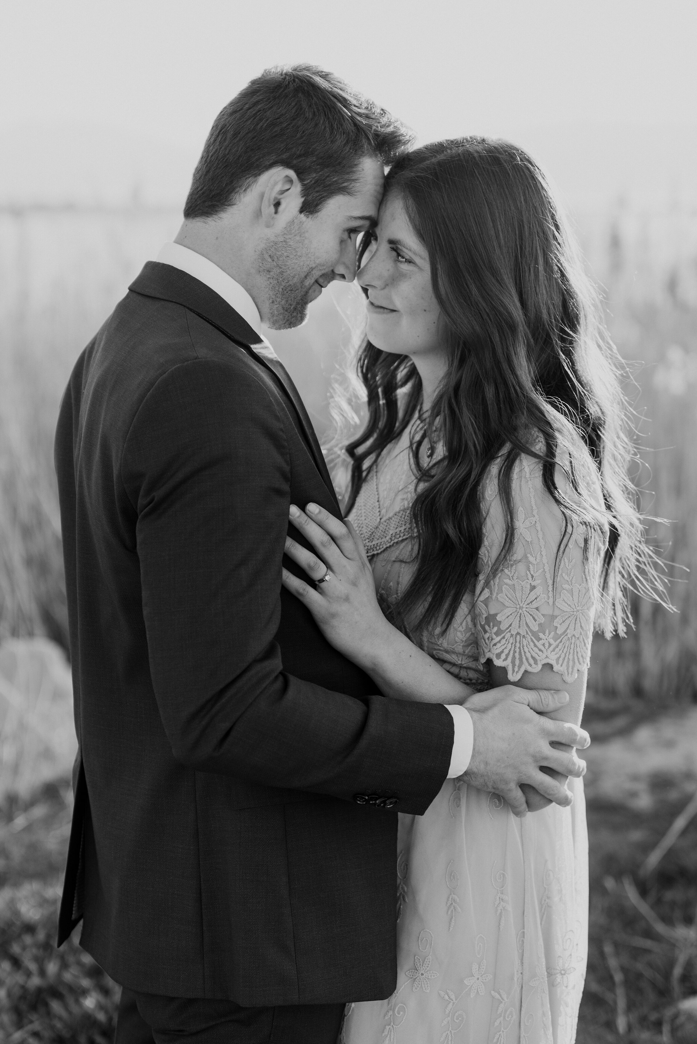 Happy couple blissfully looks at one another in a black and white photo during their engagement photoshoot. black and white photos romantic engagement photography swoonworthy photos couple pose ideas pinterest-worthy photos utah engagement photos blissful photography #coupleposes #engagementinspiration #unforgettable #foreverstartsnow #ldsweddings #blackandwhite #blackandwhitephotos