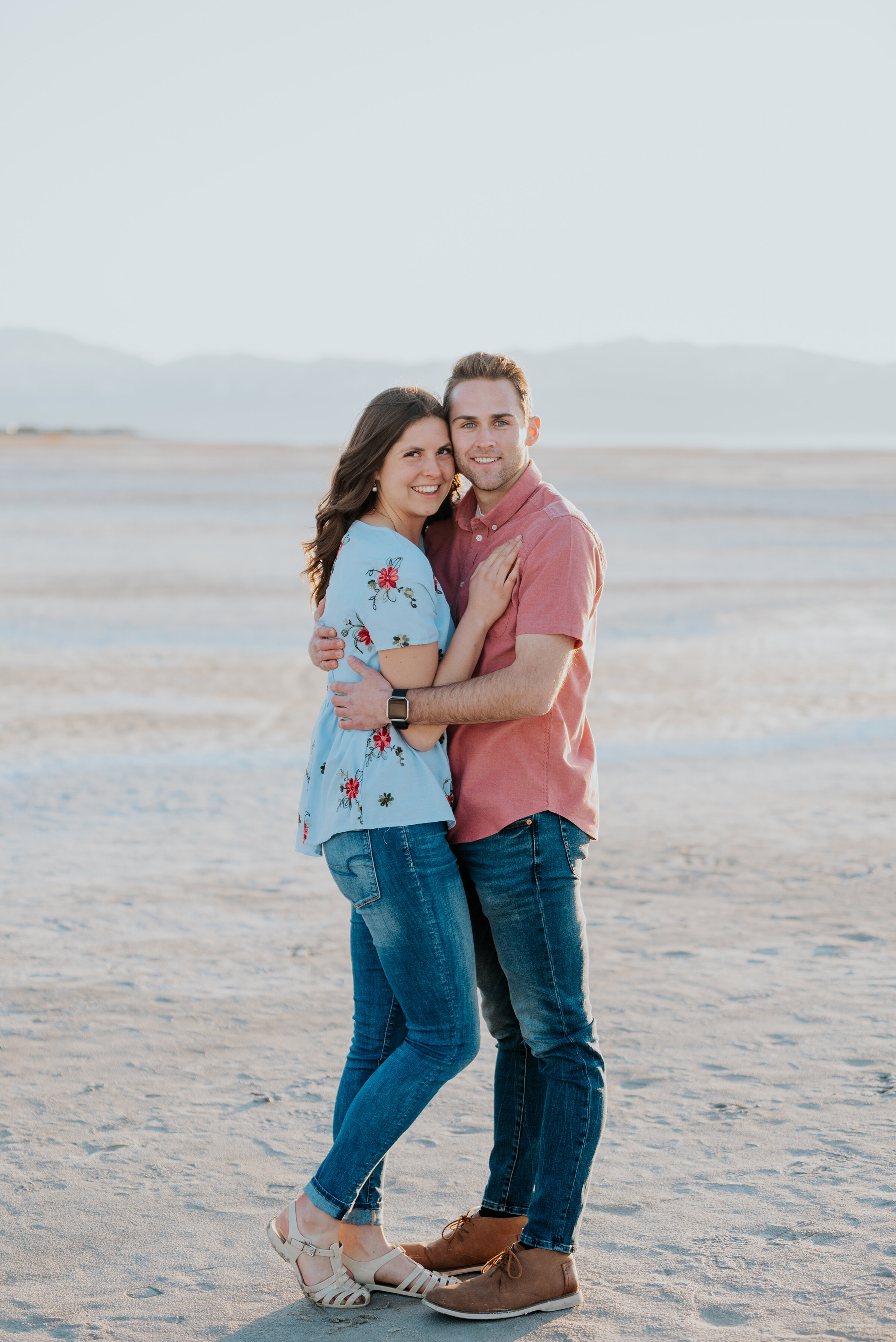 Couple looks across the salt flats in magna utah during their engagement photoshoot with Kristi Alyse Photography. Dry lake bed aesthetic magna utah photo locations outdoor nature engagement inspiration teal and coral matching outfits #kristialysephotography #tealandcoral #engagementphotoshoot #engagements #photoinspo #saltflats #utahphotography #outdoorphotography #naturephotography #natureinspo