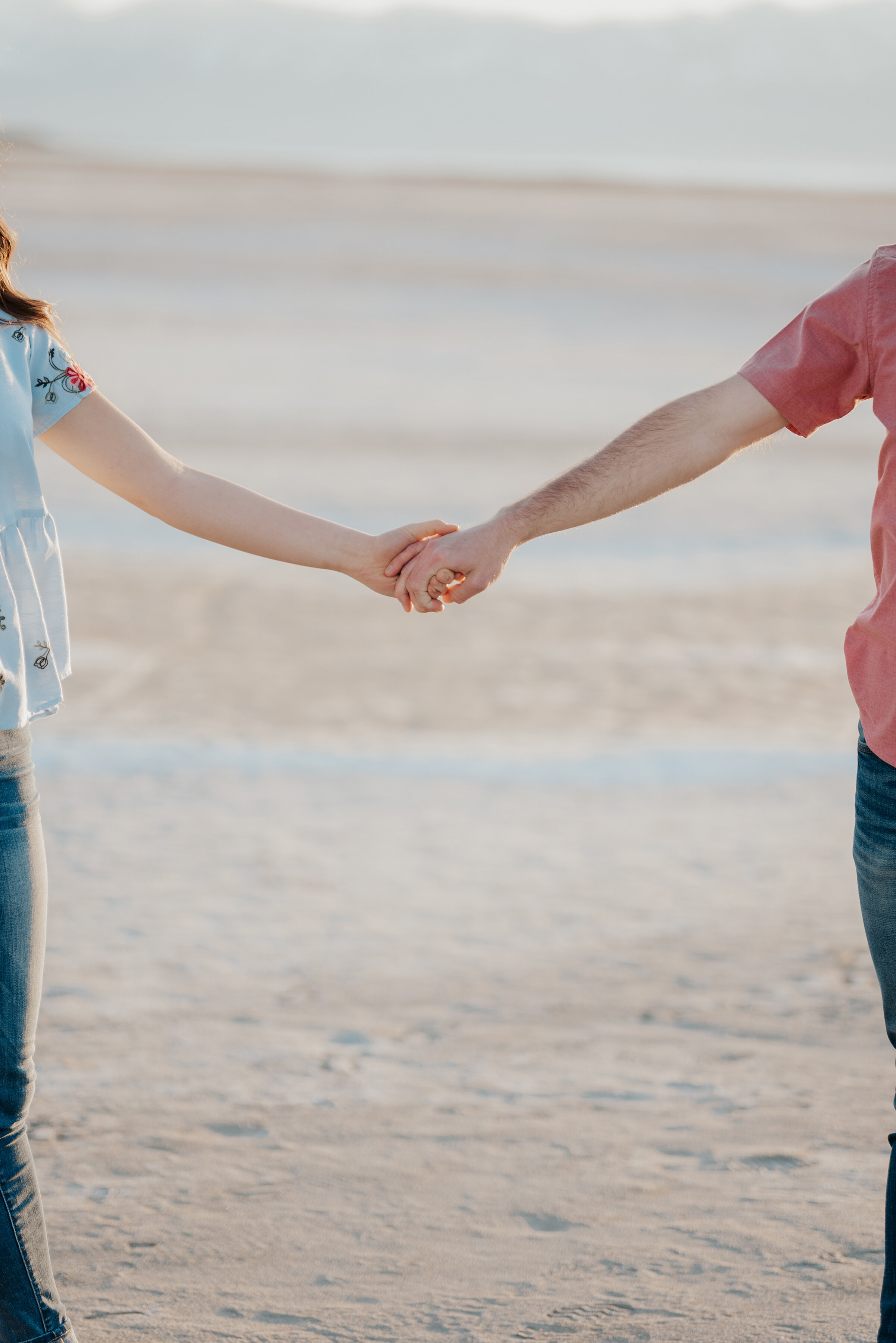 Adorable couple holds hand in an abstract engagement photo of them holding hands on the Salt Flats in Utah. Holding hands photo ideas romantic engagement photos inspiration salt flats in utah magna utah salt lake engagement photographer wedding photography best utah county wedding photographer #weddingphotography #saltflats #magnautah #engagements #photographer #engagementinspo #kristialysephotography #casualengagements