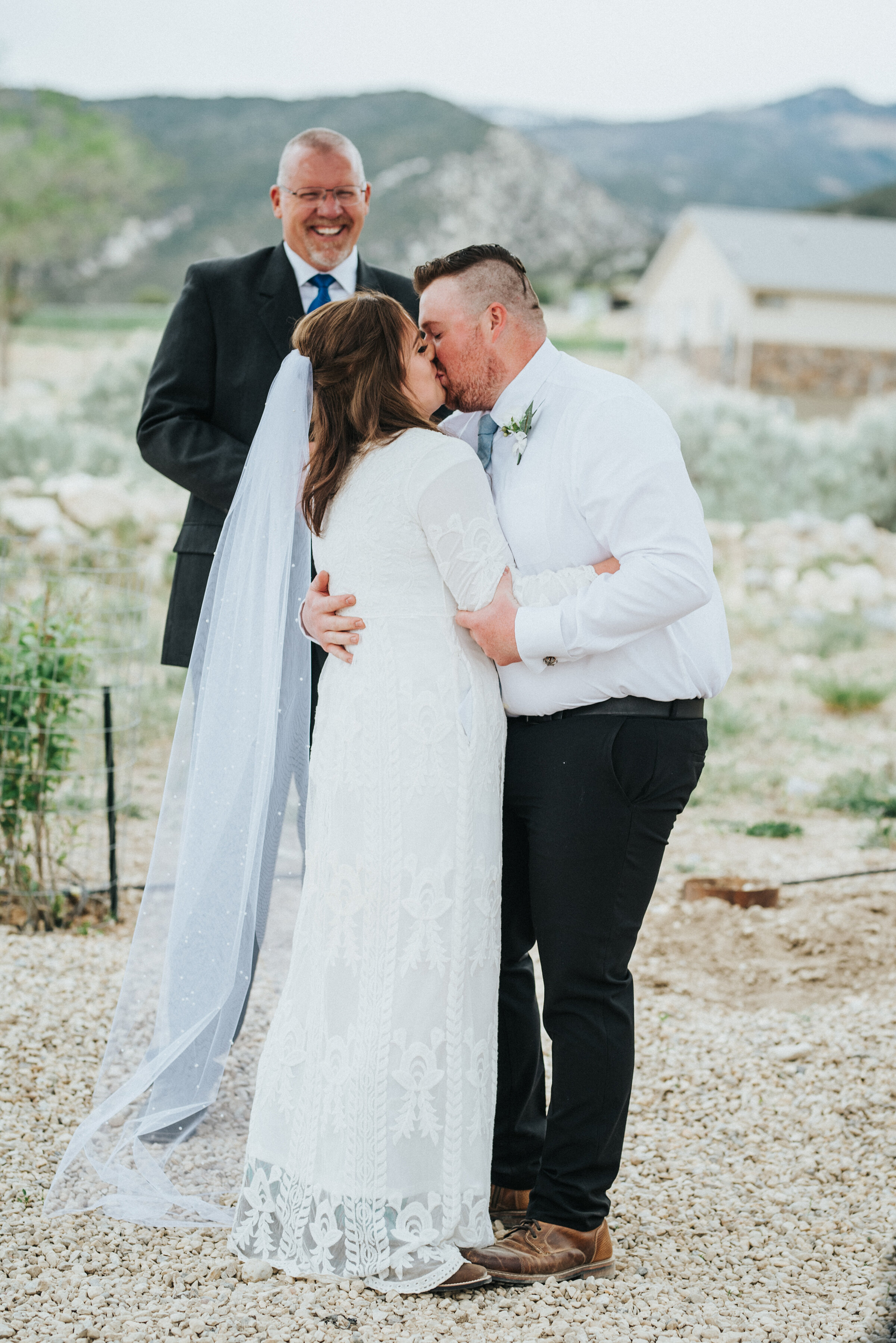 The beautiful outdoor ceremony for this western bride and groom was sealed with a kiss during their intimate wedding in Ephraim Utah.  photoshoot in Ephraim Utah photography wedding outdoor location western inspired rustic Airbnb photo aesthetic #ephraimutah #utahphotography #weddingdayphotography #gettingmarried #rusticwedding #utahwedding #westernstyle #weddingphotoshoot