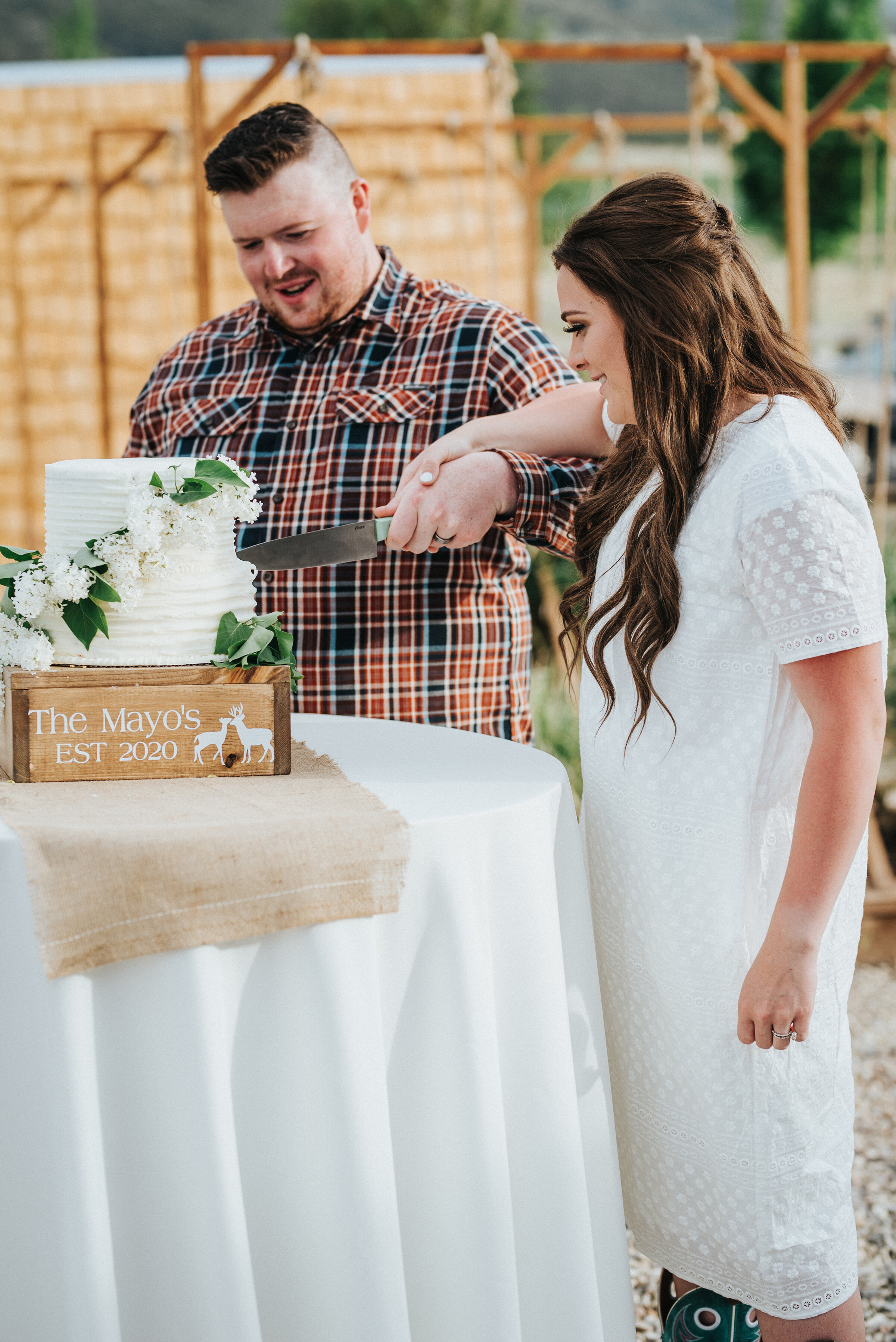 As a tradition, the bride and groom cut the gorgeous and simple wedding cake to share on their wedding day! photoshoot in Ephraim Utah photography wedding outdoor location western inspired rustic Airbnb photo aesthetic #ephraimutah #utahphotography #weddingdayphotography #gettingmarried #rusticwedding #utahwedding #westernstyle #weddingphotoshoot