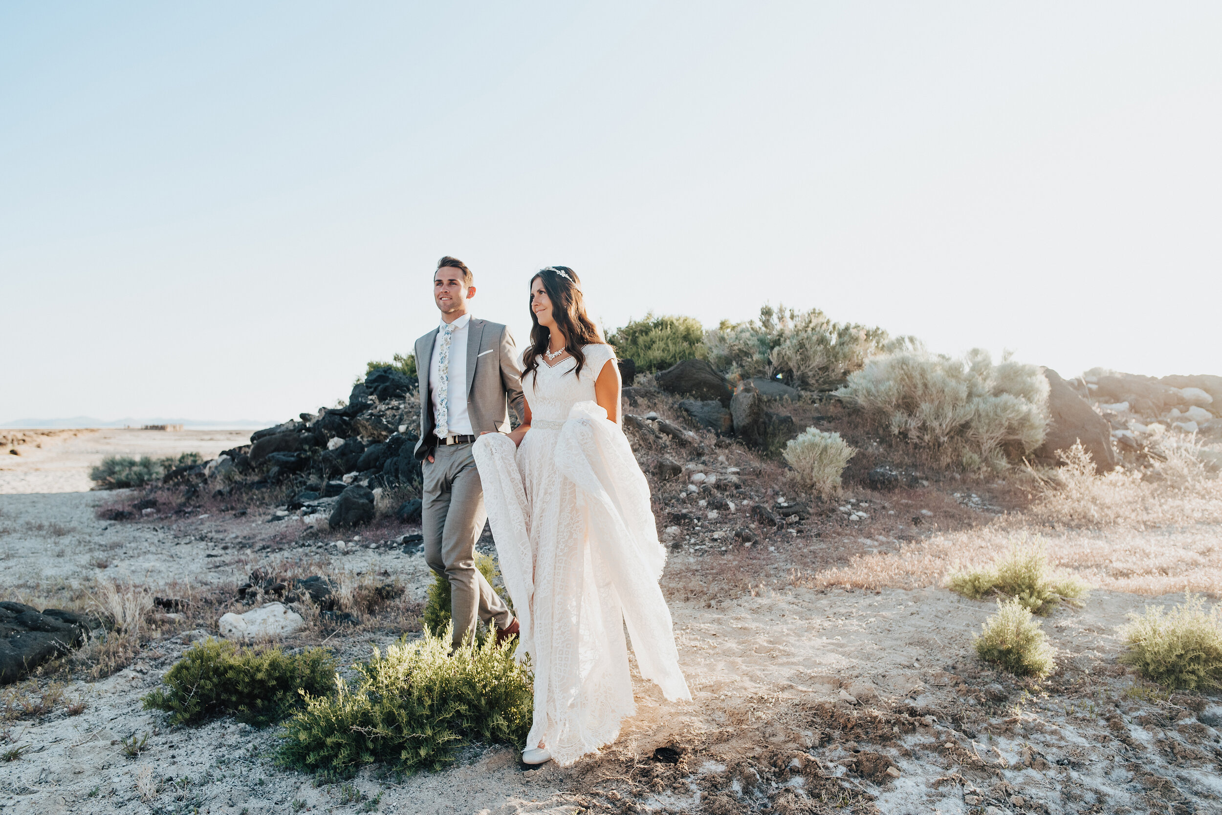 Walking down the rocky shore of the Great Salt Lake during a magical sunset formal session with this stunning bride and groom. Her lace wedding gown captured the lighting of the sunset in all the best ways and his grey suit was was made for this location. #spiraljetty #GreatSaltLake #formalsession #SaltFlats #sunsetphotosession #NorthernUtah #weddingphotographer #formalphotographer #brideandgroom #outdoorformals #weddingformalphotography