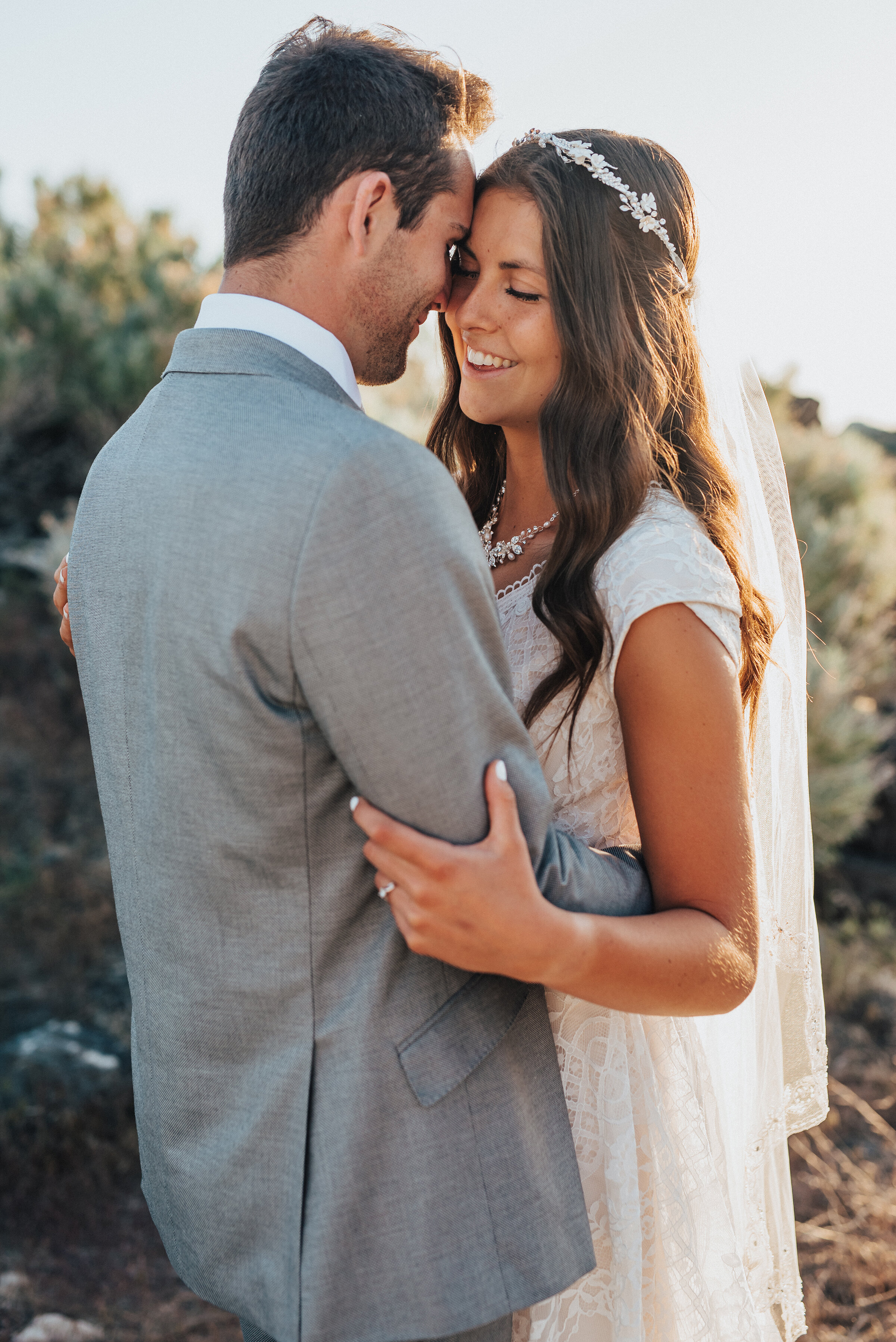 Her smile says a thousand words as the sun dances across her long cathedral veil at the Spiral Jetty in Northern Utah. elegant sweet formal session great salt lake utah photographer #spiraljetty #GreatSaltLake #formalsession #SaltFlats #sunsetphotosession #NorthernUtah #weddingphotographer #formalphotographer #brideandgroom #outdoorformals #weddingformalphotography
