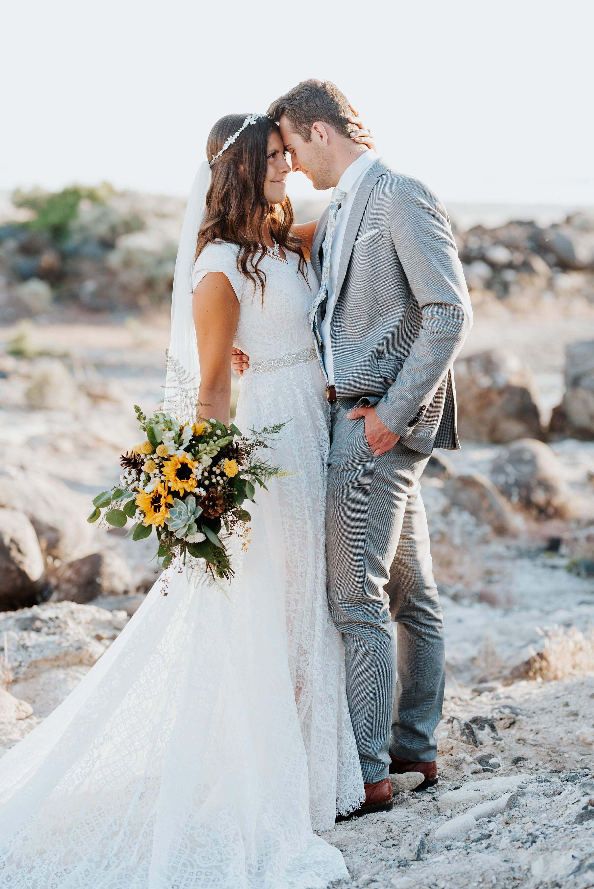 The bride's sunflower bouquet was gorgeous as the bride and groom stood on the sandy shore of the Great Salt Lake with the rocky Spiral Jetty surrounding them. #spiraljetty #GreatSaltLake #formalsession #SaltFlats #sunsetphotosession #NorthernUtah #weddingphotographer #formalphotographer #brideandgroom #outdoorformals #weddingformalphotography