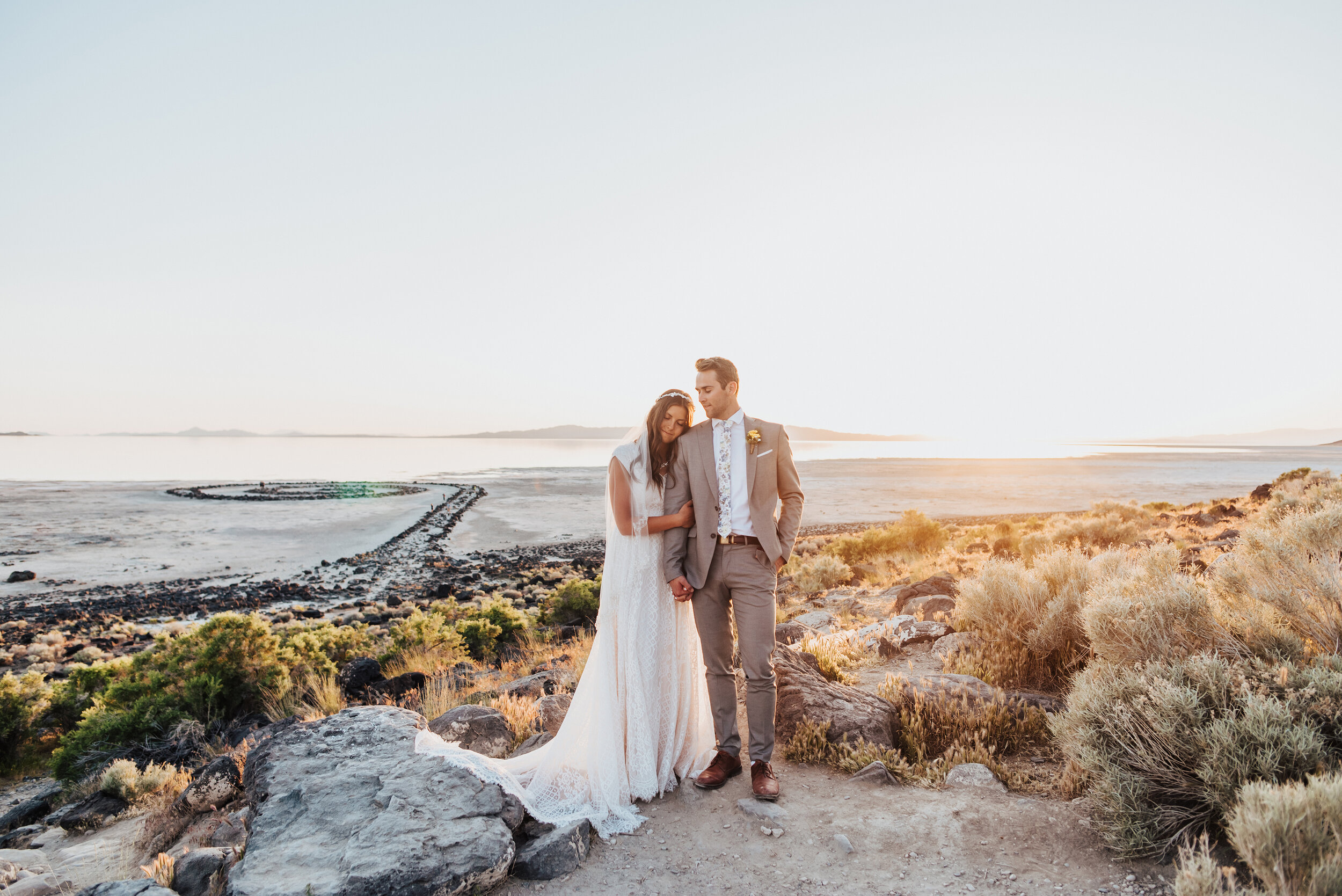 The sunset could not have painted a picture any more gorgeous than during this sunset formal session for the stunning bride and groom at the Spiral Jetty. #spiraljetty #GreatSaltLake #formalsession #SaltFlats #sunsetphotosession #NorthernUtah #weddingphotographer #formalphotographer #brideandgroom #outdoorformals #weddingformalphotography