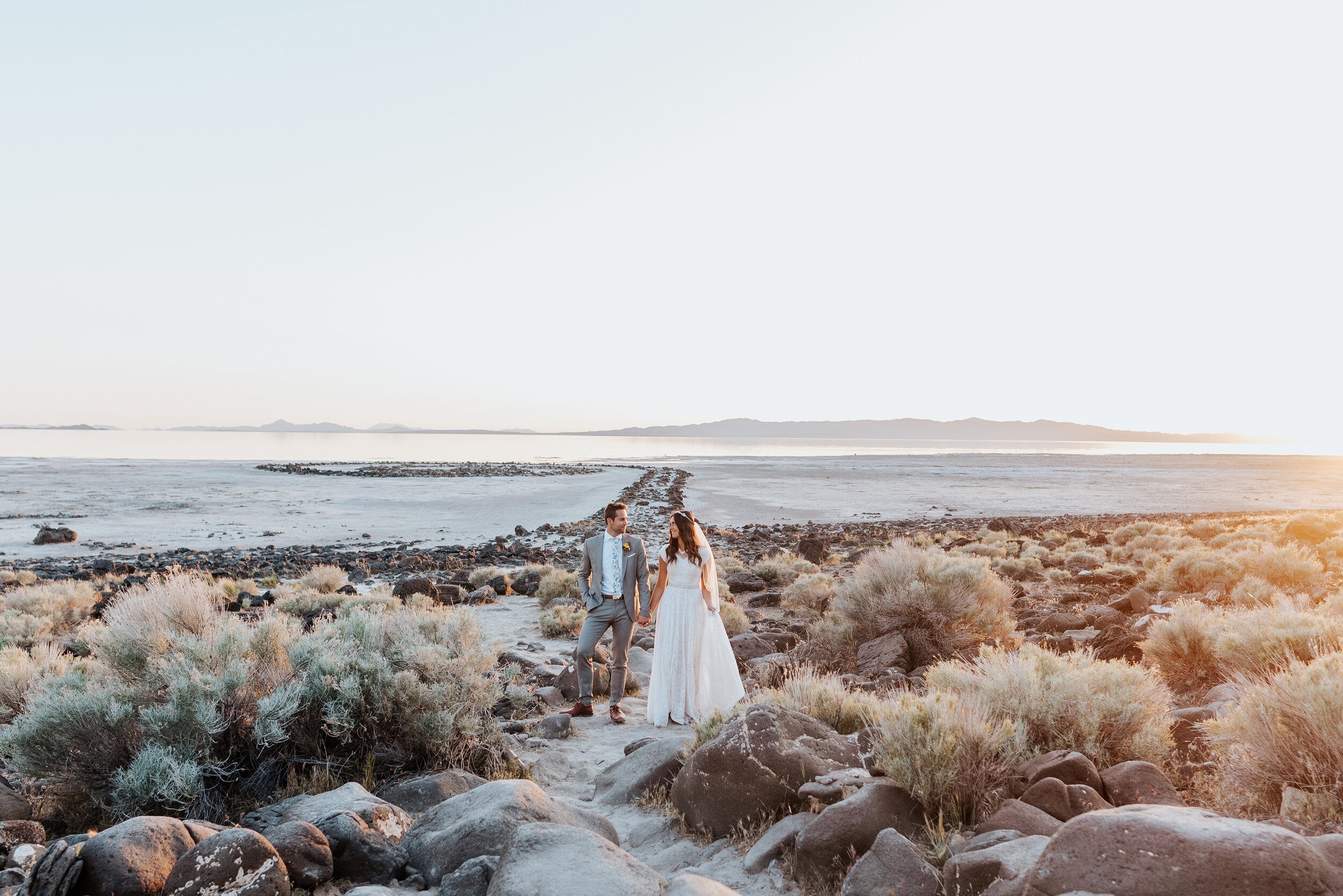 With the last glimpses of the sun shining just beyond the waters edge, this bride and groom stood with a stunning backdrop and held each other with excitement. wedding formal session utah wedding photographer formal session #spiraljetty #GreatSaltLake #formalsession #SaltFlats #sunsetphotosession #NorthernUtah #weddingphotographer #formalphotographer #brideandgroom #outdoorformals #weddingformalphotography
