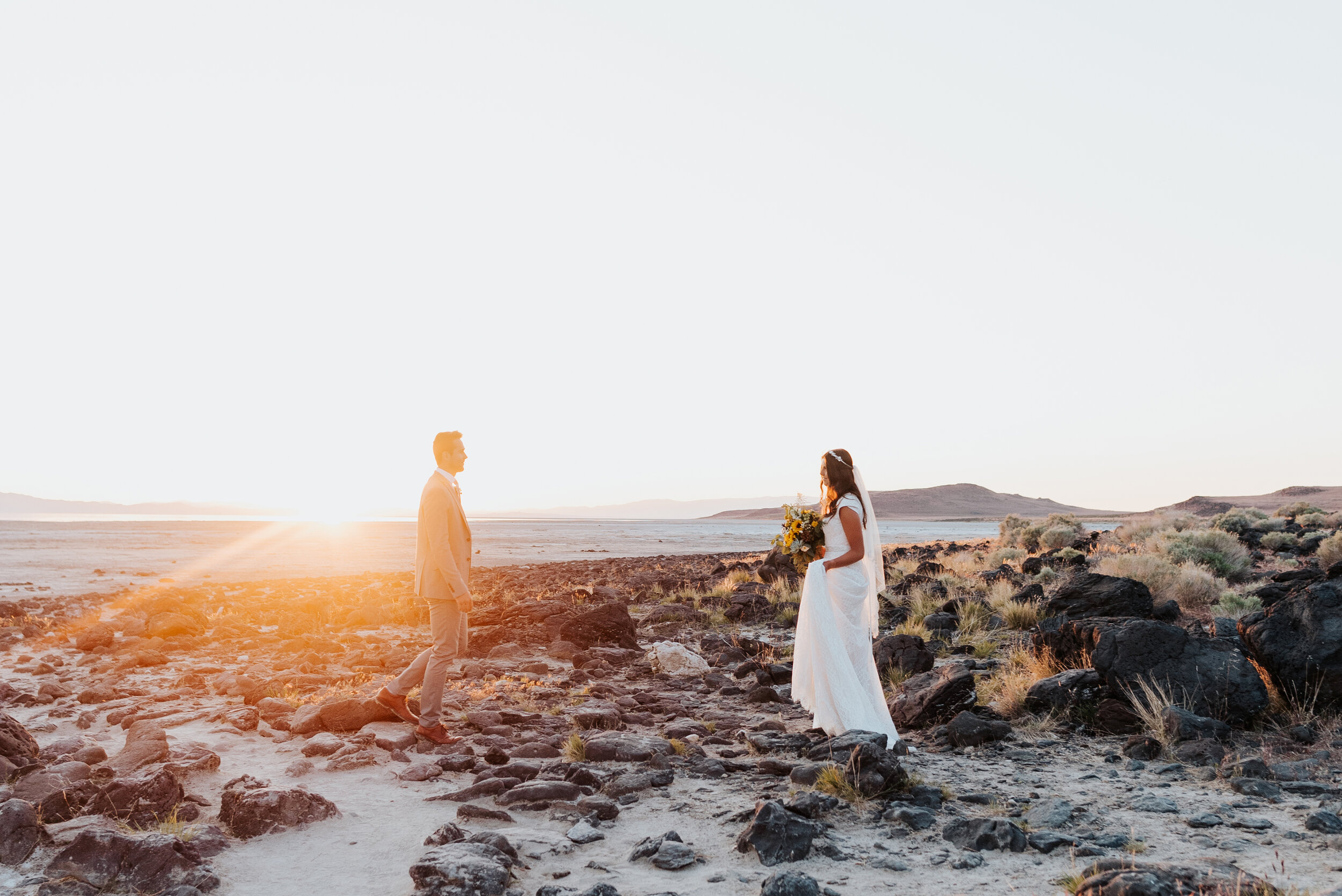 Walking toward each other across the rocky shore of the Spiral Jetty, this bride and groom were thrilled to enjoy their formal session dressed in their wedding clothes in anticipation for their wedding day! #spiraljetty #GreatSaltLake #formalsession #SaltFlats #sunsetphotosession #NorthernUtah #weddingphotographer #formalphotographer #brideandgroom #outdoorformals #weddingformalphotography