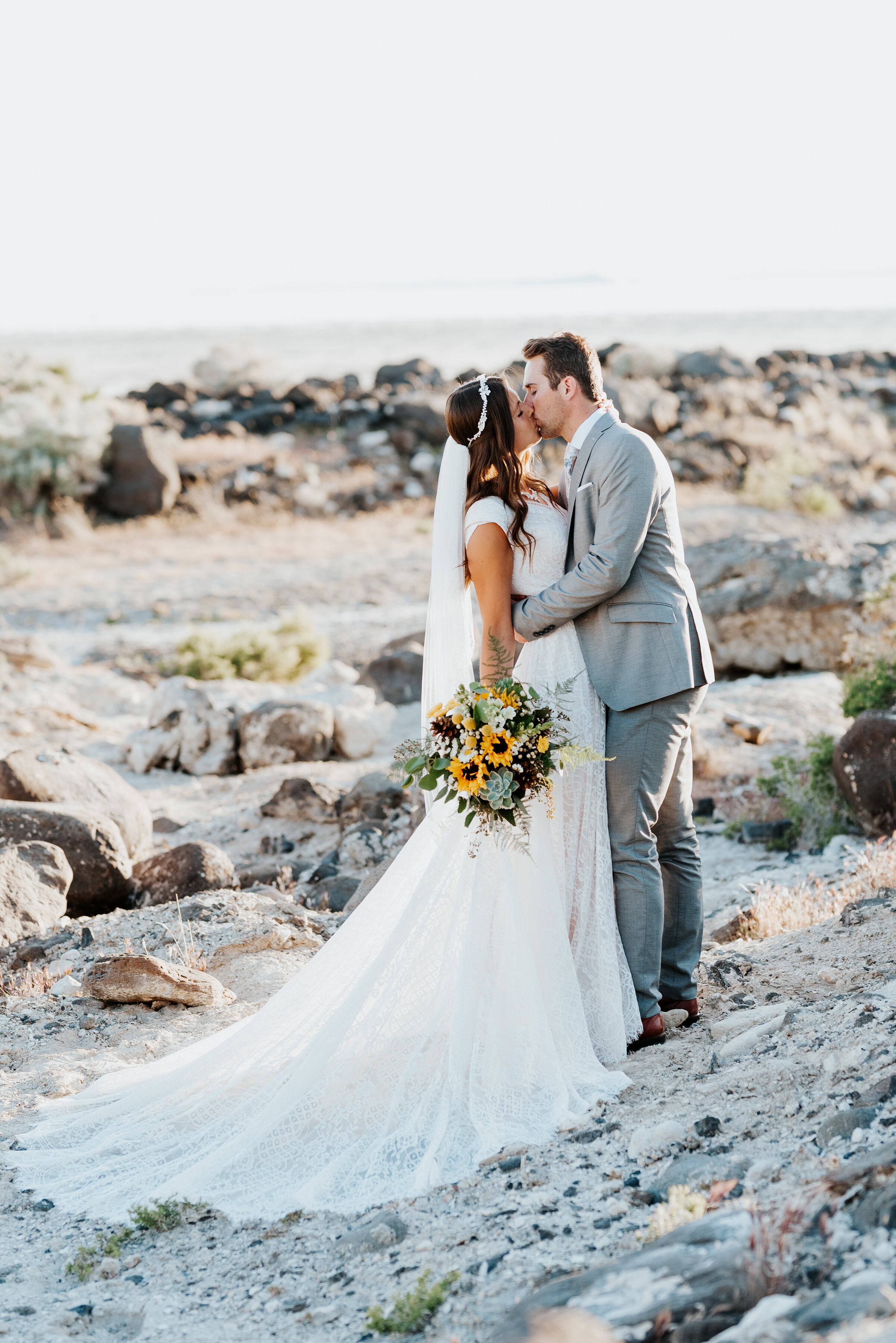 Bride and groom share an intimate kiss at their sunset session at the Great Salt Lake Spiral Jetty. sunflowers gorgeous rocky shore northern utah #spiraljetty #GreatSaltLake #formalsession #SaltFlats #sunsetphotosession #NorthernUtah #weddingphotographer #formalphotographer #brideandgroom #outdoorformals #weddingformalphotography