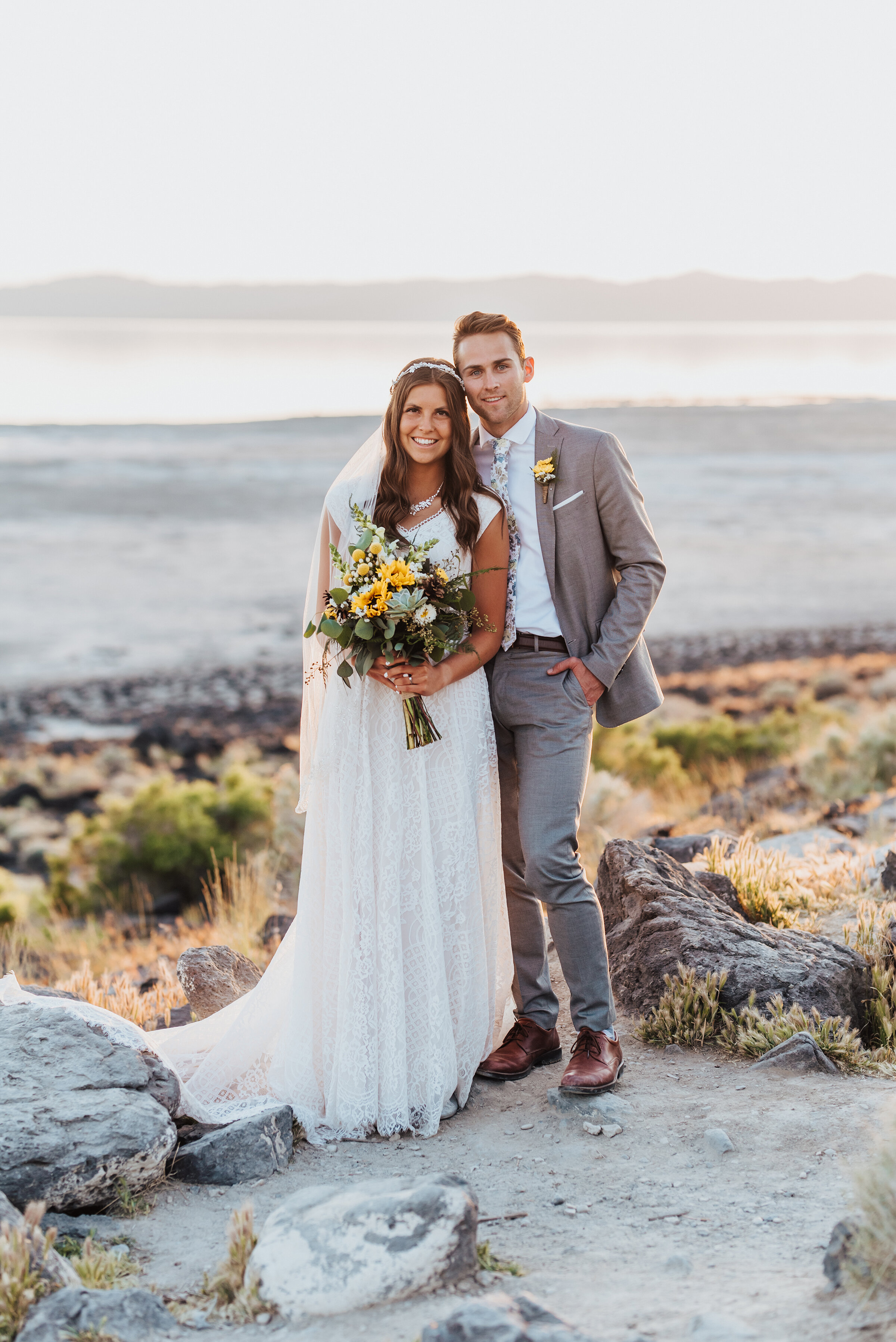 Smiling portrait photo of the bride and groom at the Great Salt Lake Spiral Jetty with bright yellow sunflowers in the brides bouquet. #spiraljetty #GreatSaltLake #formalsession #SaltFlats #sunsetphotosession #NorthernUtah #weddingphotographer #formalphotographer #brideandgroom #outdoorformals #weddingformalphotography
