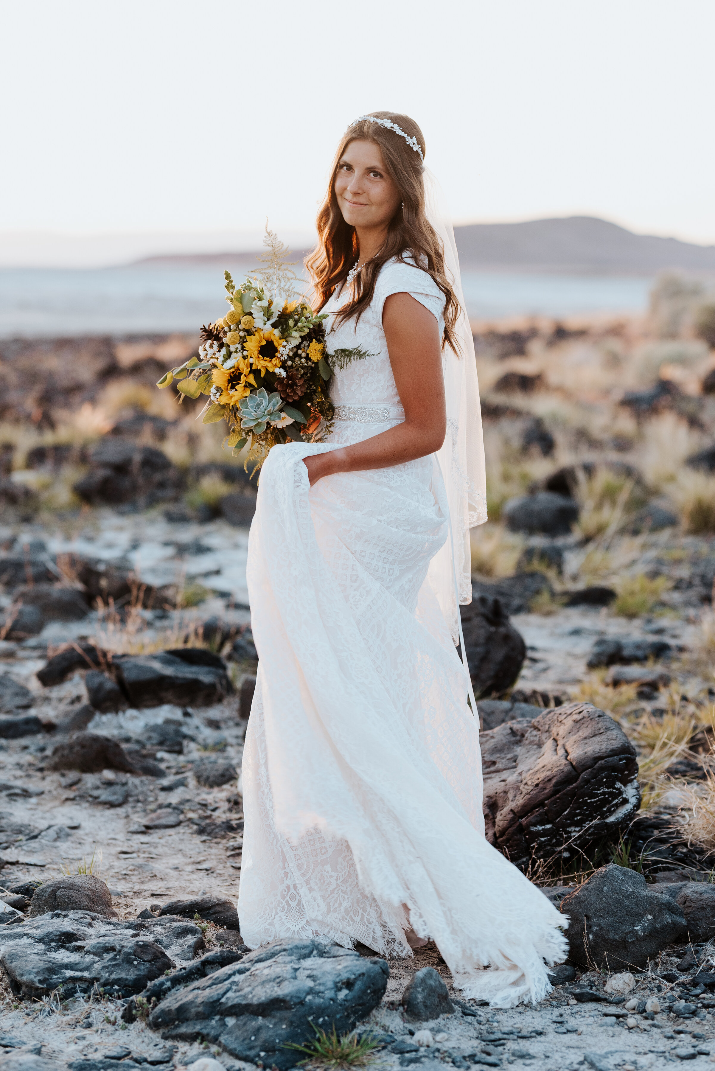 The stunning bride walking across the rocky Spiral Jetty shore with her sunflower bouquet and halo headband holding her gorgeous veil. #spiraljetty #GreatSaltLake #formalsession #SaltFlats #sunsetphotosession #NorthernUtah #weddingphotographer #formalphotographer #brideandgroom #outdoorformals #weddingformalphotography
