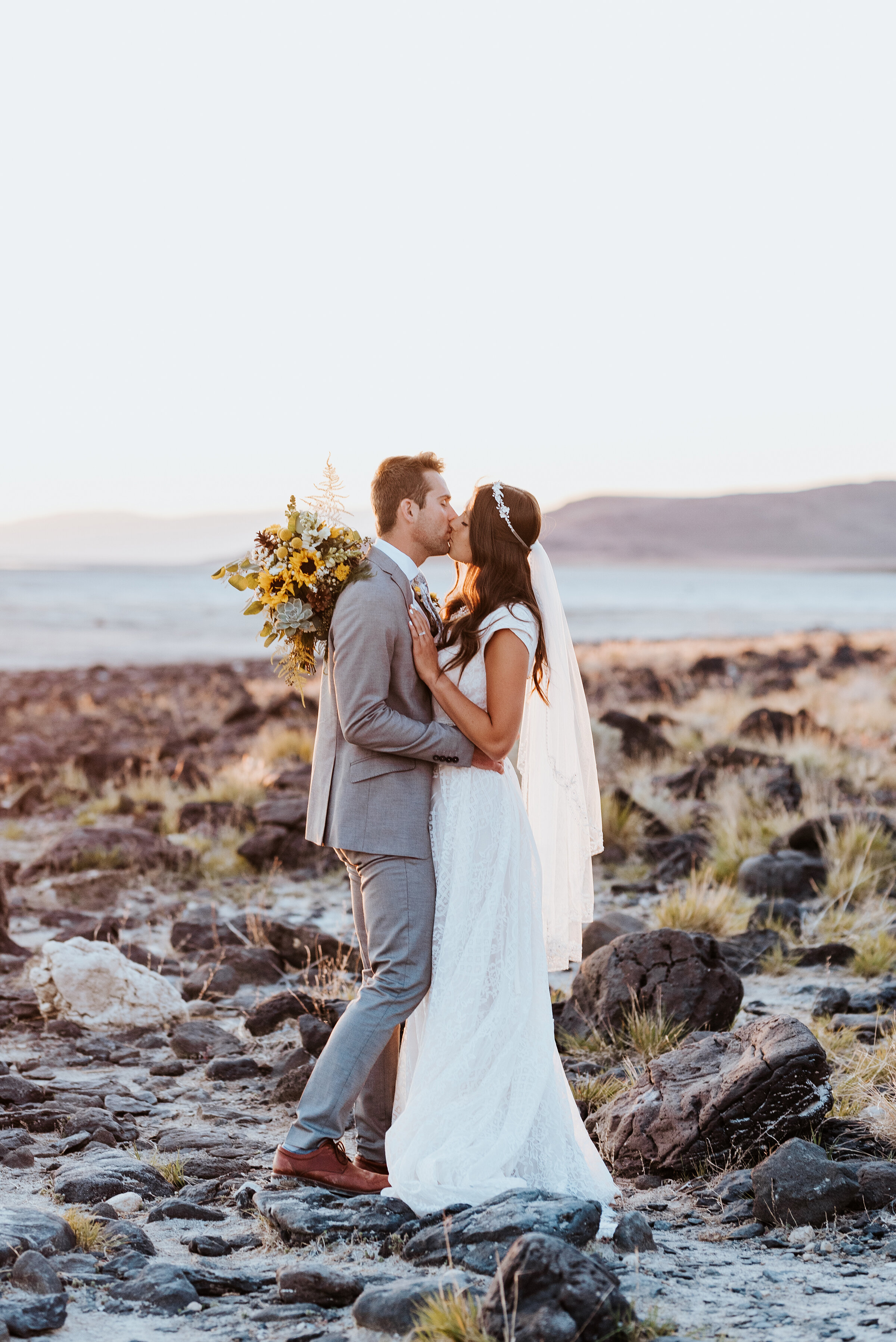 The bride and groom share a kiss just off the shore of the Great Salt Lake. The rocks provided texture to the background as the bride and groom captured the last of the sunshine rays in the distance. #spiraljetty #GreatSaltLake #formalsession #SaltFlats #sunsetphotosession #NorthernUtah #weddingphotographer #formalphotographer #brideandgroom #outdoorformals #weddingformalphotography