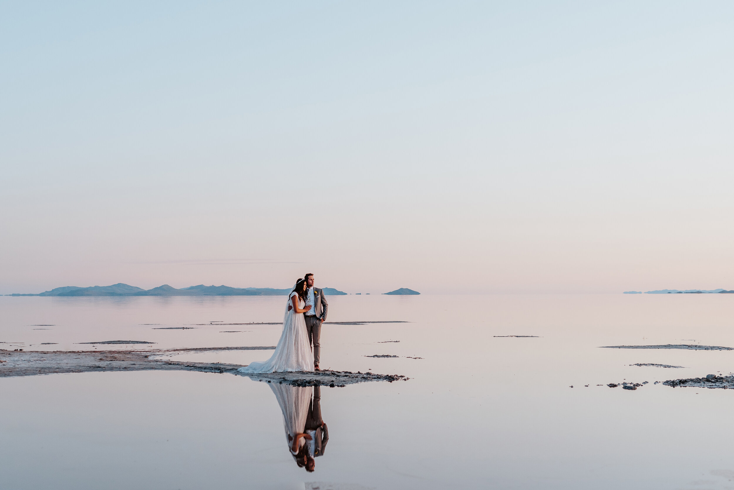 The bride and groom were surrounded by water as their reflection is captured flawlessly without any wind at the Great Salt Lakes. #spiraljetty #GreatSaltLake #formalsession #SaltFlats #sunsetphotosession #NorthernUtah #weddingphotographer #formalphotographer #brideandgroom #outdoorformals #weddingformalphotography