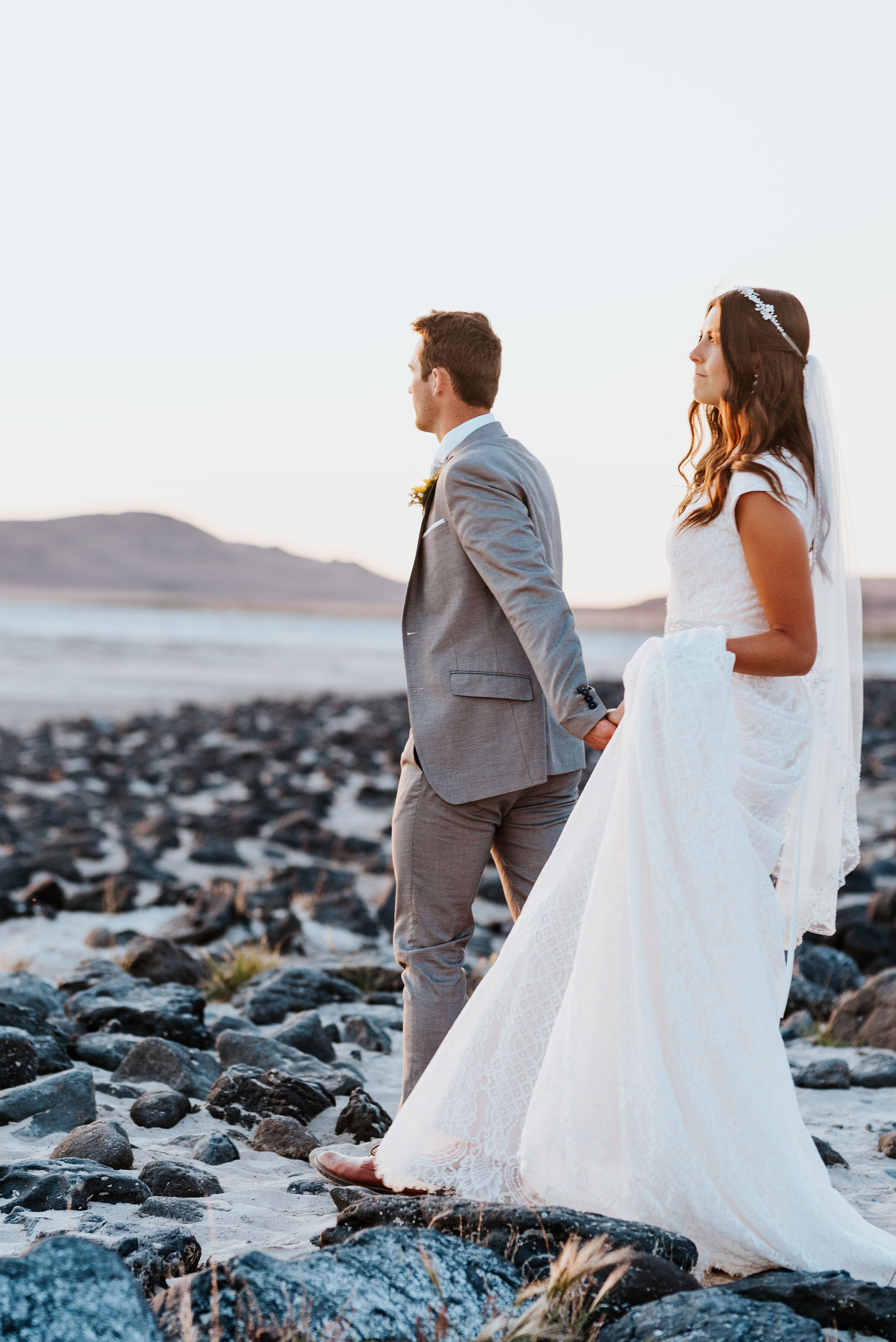 Bride and groom walking across the rocky shore of The Great Salt Lake Spiral Jetty taking in the last of the sunset before it fades behind the mountains in the distance. #spiraljetty #GreatSaltLake #formalsession #SaltFlats #sunsetphotosession #NorthernUtah #weddingphotographer #formalphotographer #brideandgroom #outdoorformals #weddingformalphotography