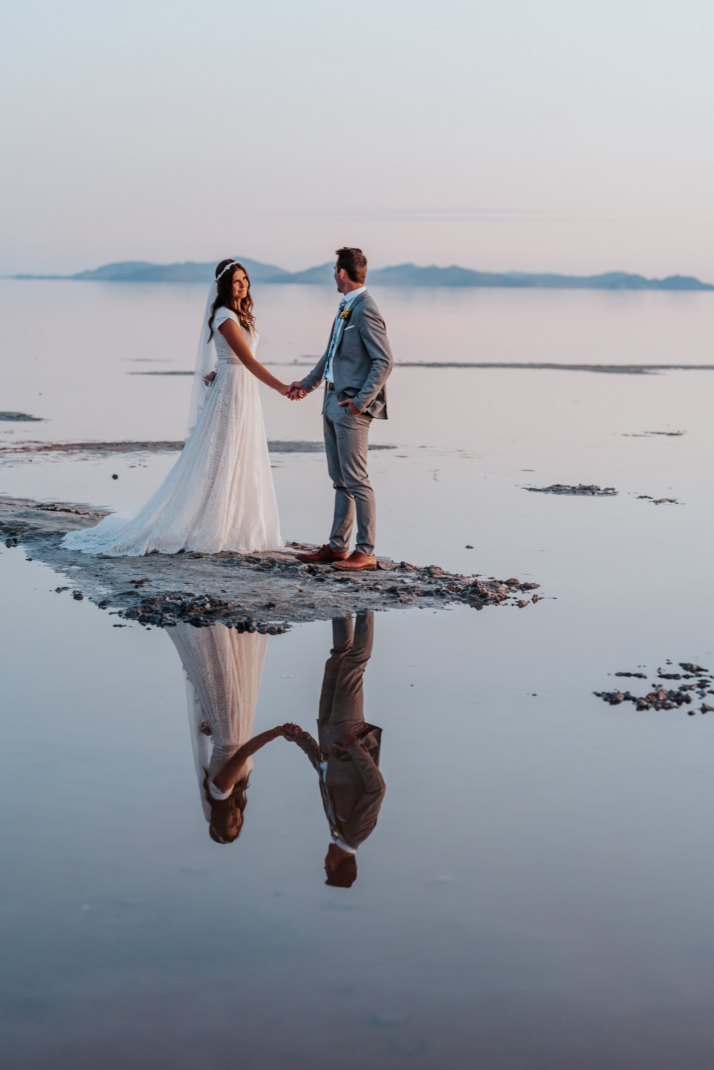 Flawless reflection of the bride and groom holding hands in the water of the Great Salt Lake Spiral Jetty. reflection water formal session sunset wedding photography #spiraljetty #GreatSaltLake #formalsession #SaltFlats #sunsetphotosession #NorthernUtah #weddingphotographer #formalphotographer #brideandgroom #outdoorformals #weddingformalphotography