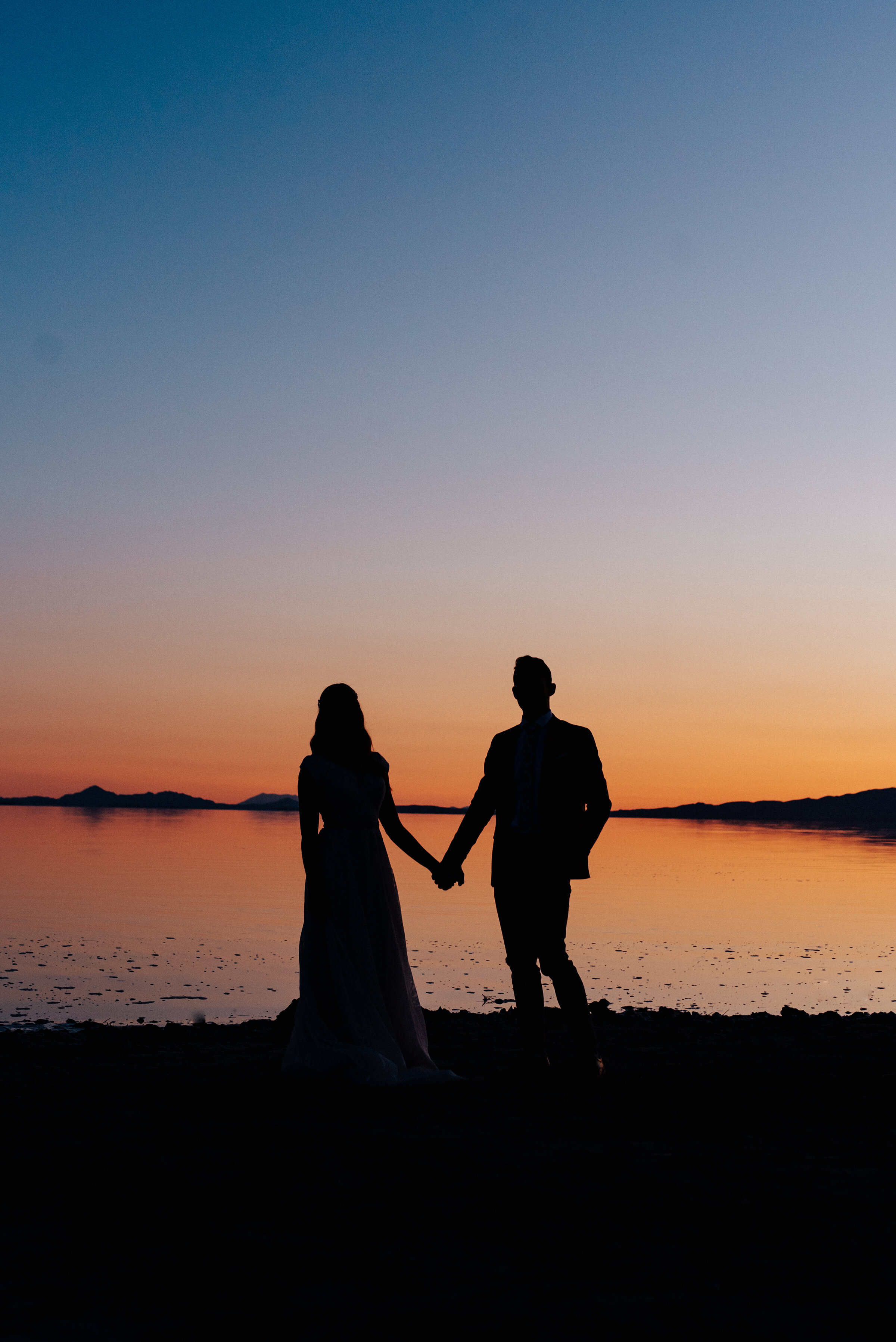 Silhouettes of the bride and groom at sunset during their formal wedding photography session at the Great Salt Lake Spiral Jetty. #spiraljetty #GreatSaltLake #formalsession #SaltFlats #sunsetphotosession #NorthernUtah #weddingphotographer #formalphotographer #brideandgroom #outdoorformals #weddingformalphotography