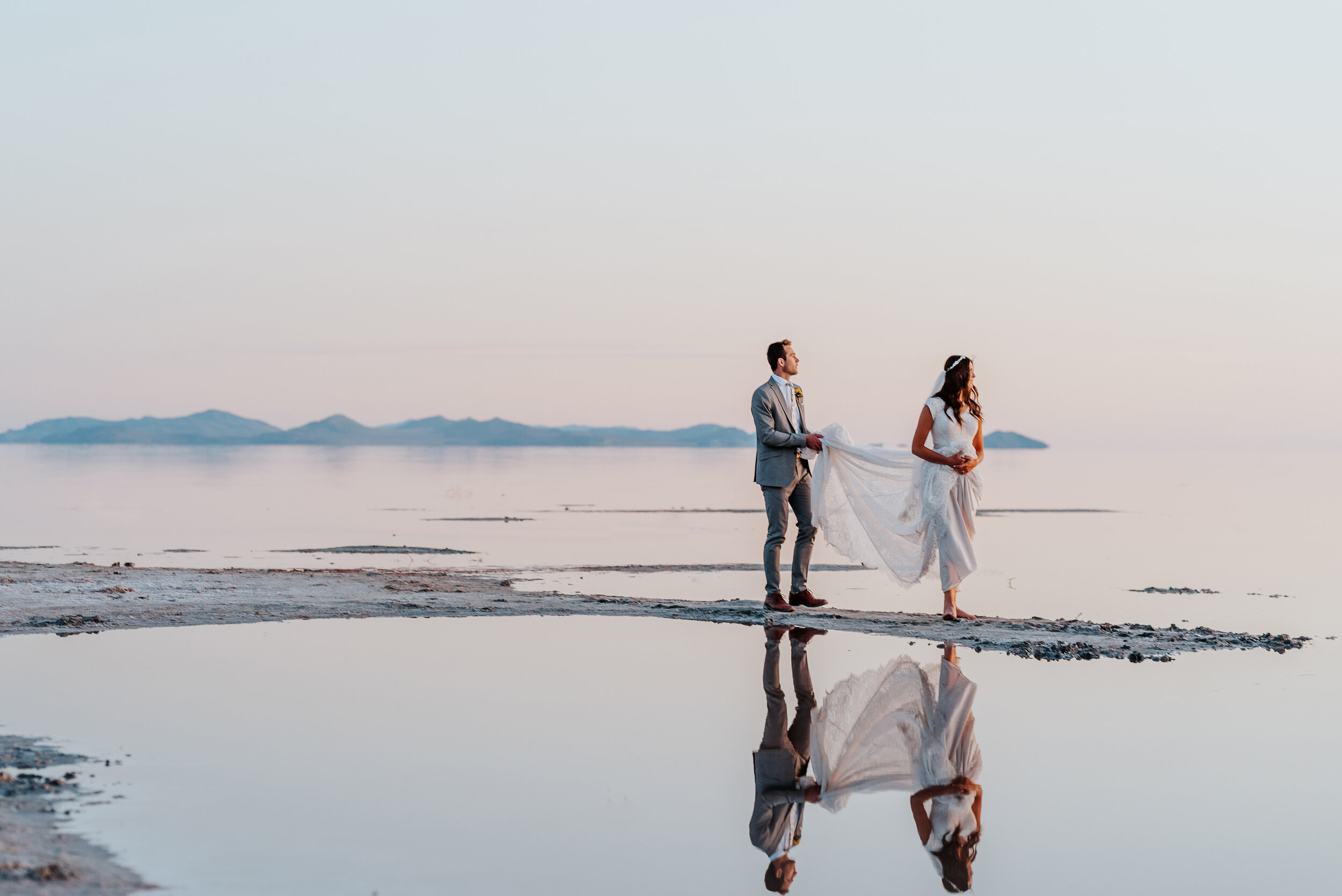 The bride and groom enjoying the last of the sunshine during their formal wedding photography session in Northern Utah. wedding photographer formal session water formals #spiraljetty #GreatSaltLake #formalsession #SaltFlats #sunsetphotosession #NorthernUtah #weddingphotographer #formalphotographer #brideandgroom #outdoorformals #weddingformalphotography