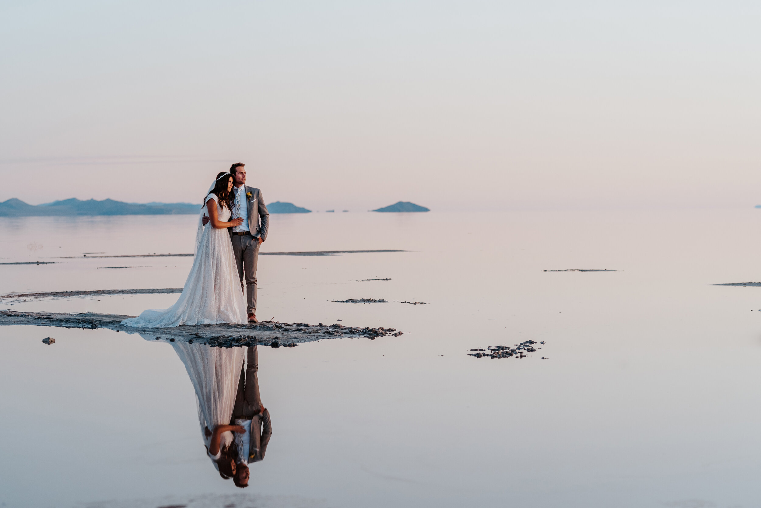 Arm in arm the bride and groom watched as the sun disappeared beyond the mountains  in the distance during their formal wedding photography session at the Spiral Jetty in Utah. #spiraljetty #GreatSaltLake #formalsession #SaltFlats #sunsetphotosession #NorthernUtah #weddingphotographer #formalphotographer #brideandgroom #outdoorformals #weddingformalphotography